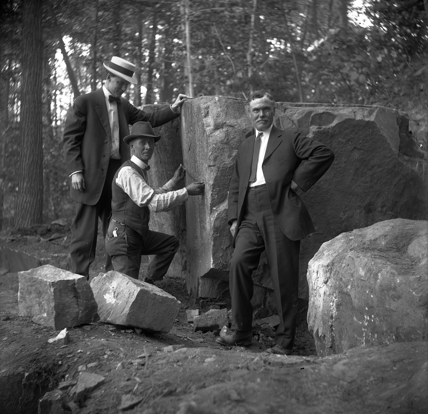 Figure 1: From left to right, Raymond Pitcairn, Edward Kessel, and Pringle Borthwick measure the cornerstone before it is split from the larger boulder.