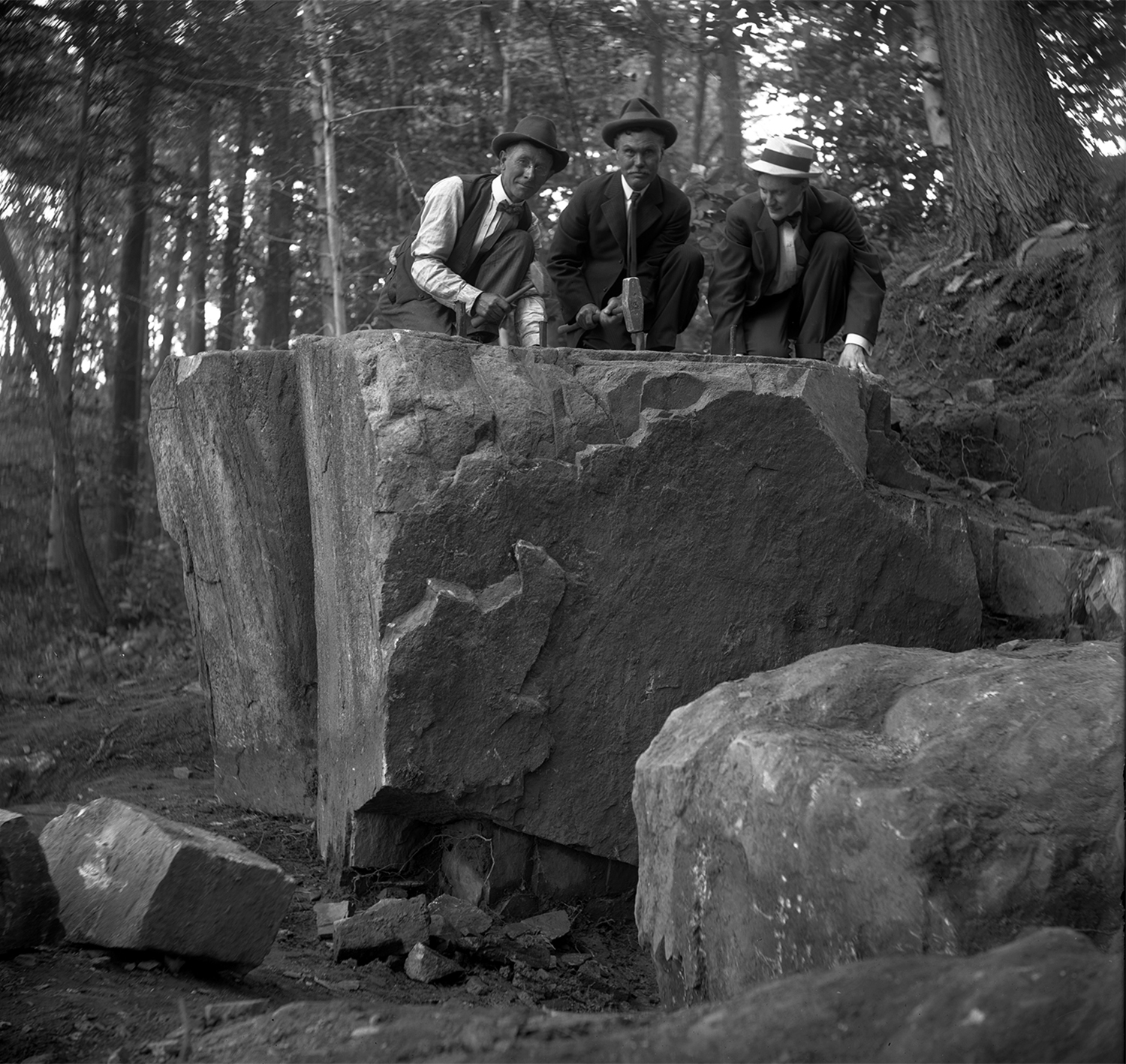 Figure 4: From left to right, Edward Kessel, Pringle Borthwick, and Raymond Pitcairn strike a pose with hammers and wedges in preparation for splitting the cornerstone from the boulder.