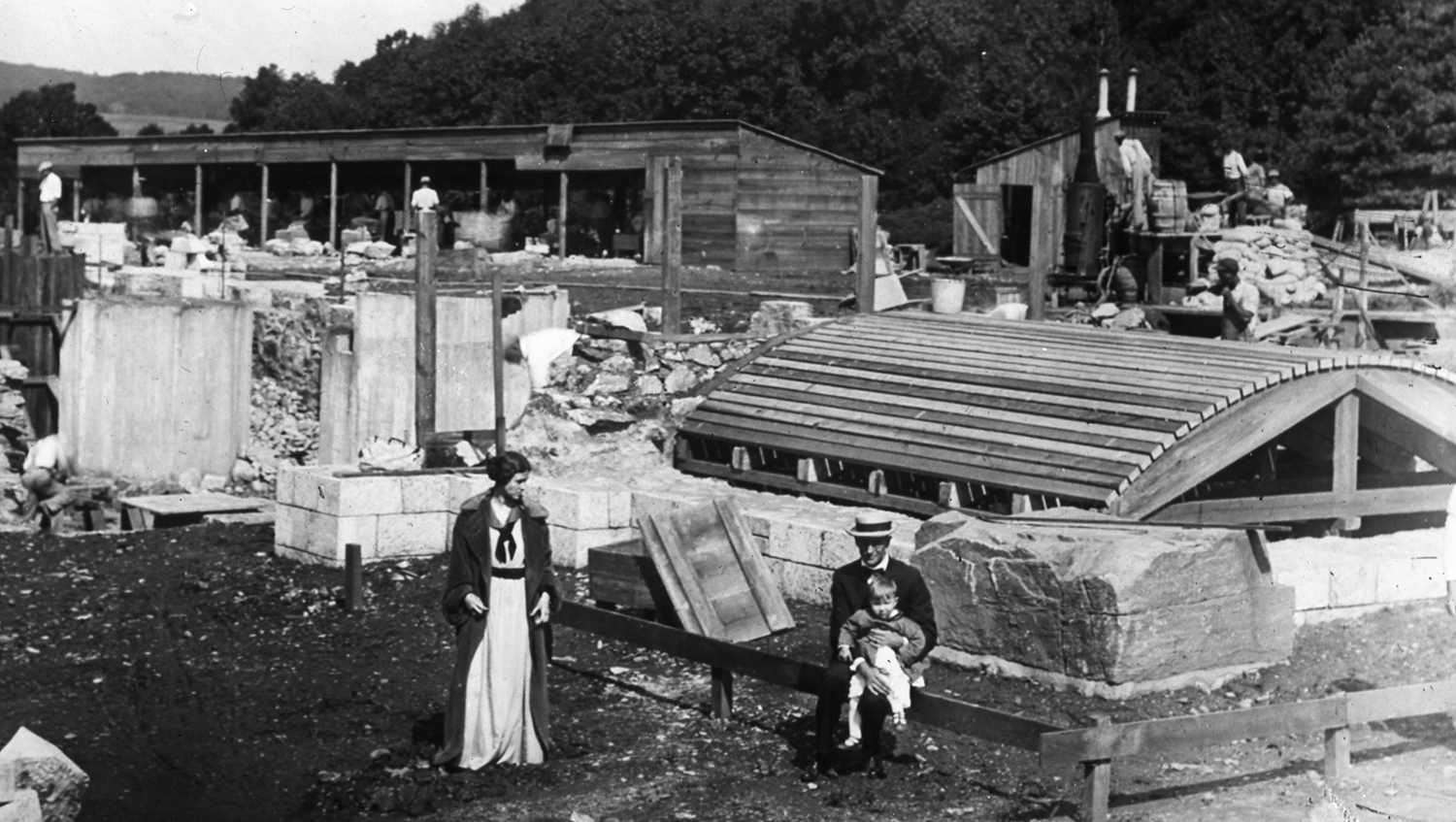 Figure 5: Mildred and Raymond Pitcairn visit the cornerstone with their son Nathan during the summer of 1914. The curved wooden structure in the photograph was a temporary frame used in the construction of an arched stone ceiling under the Cathedral's sanctuary.