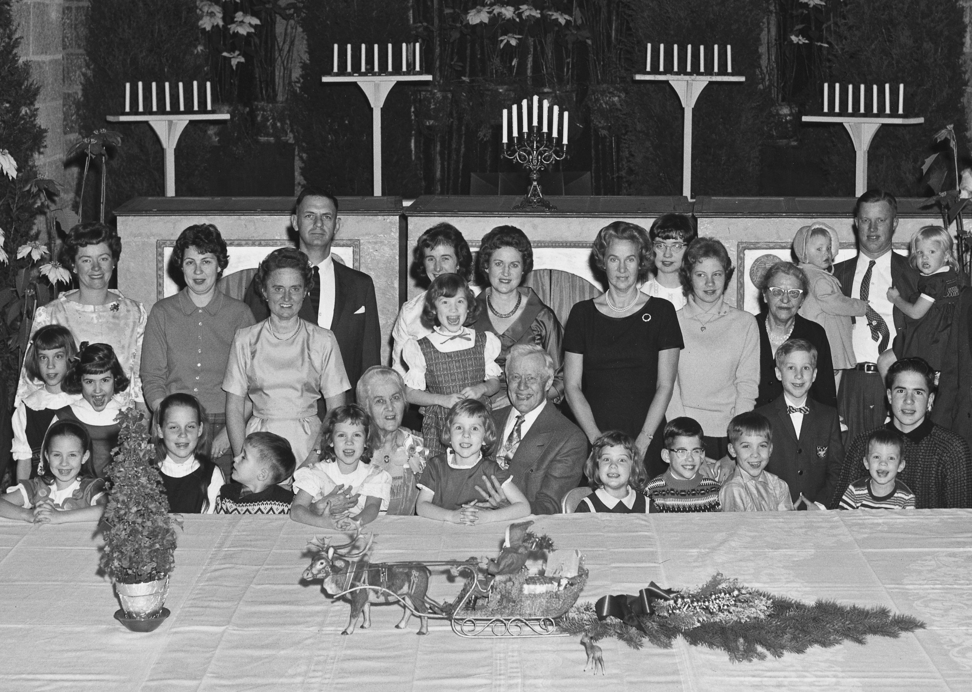 Raymond and Mildred Pitcairn pose with children and grandchildren on Christmas Day (1961) in Glencairn's Upper Hall. Santa and his reindeer are the centerpiece of the holiday table.