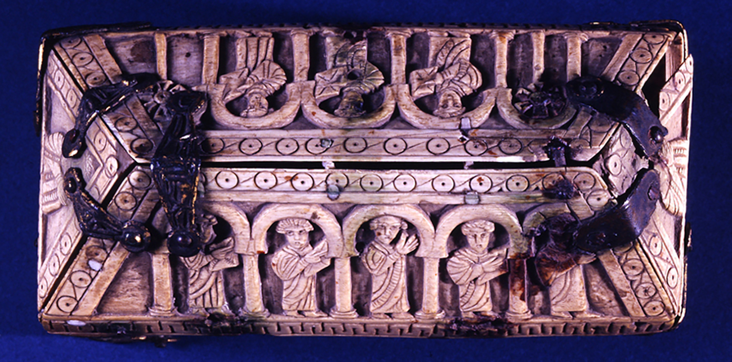 Figure 2: Lid with eight figures standing under arches. Some hold books while others raise their hands as if in prayer.