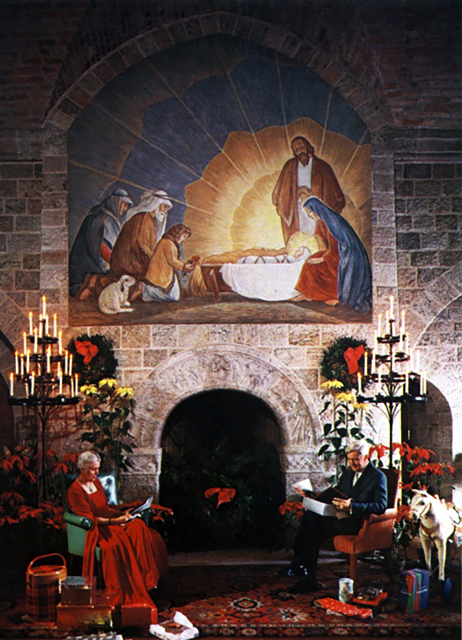 """Mildred and Raymond Pitcairn pose for their 1954 Christmas card beside the """"Seven Days of Creation"""" fireplace in Glencairn's Upper Hall. A large oil painting of the shepherds visiting the Christ Child hangs above the fireplace."""