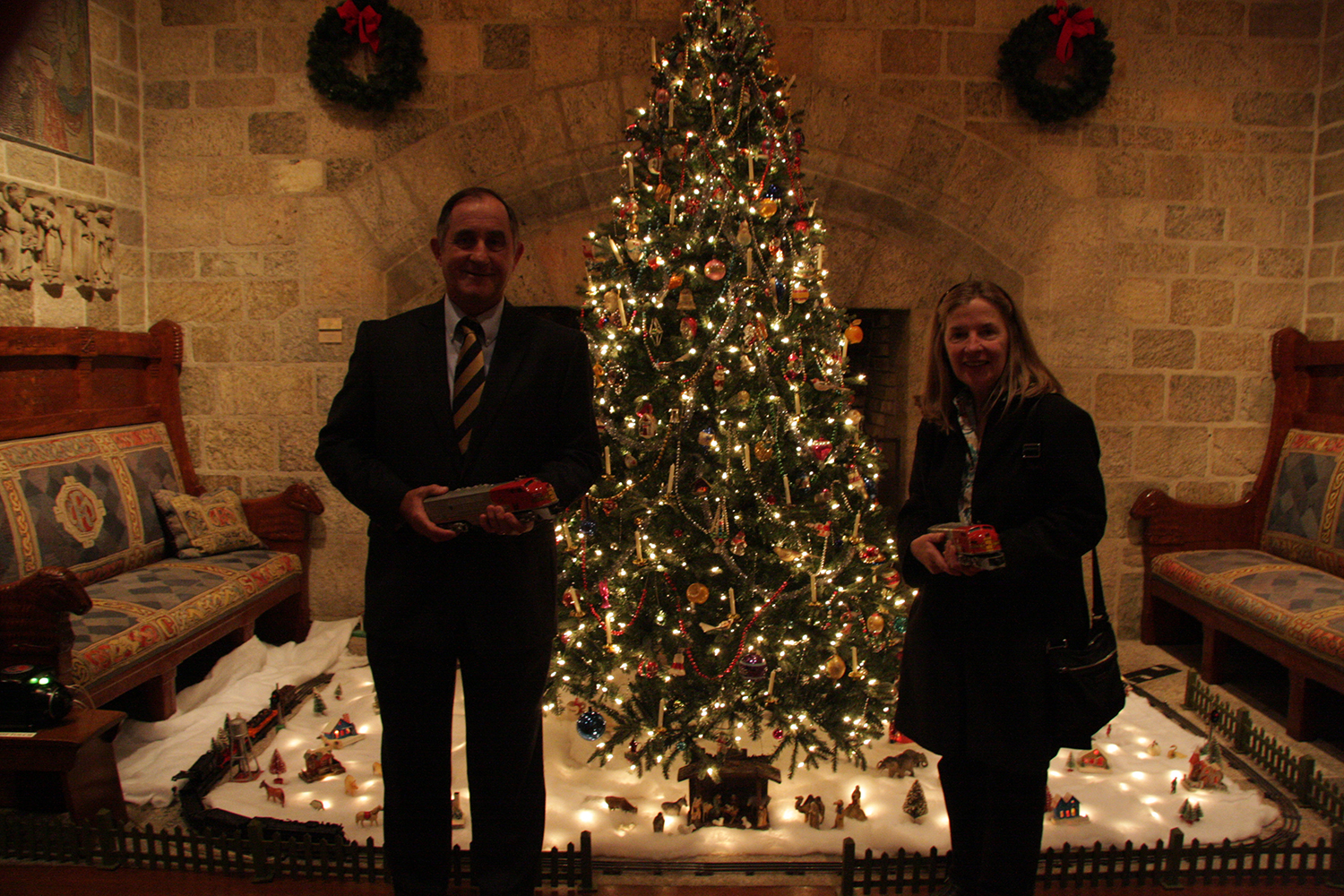 Figure 5: Steve Chardos and his sister Louise Chardos, standing by Glencairn's Christmas tree, hold two of the 1950s Lionel toy trains they donated to the Museum.