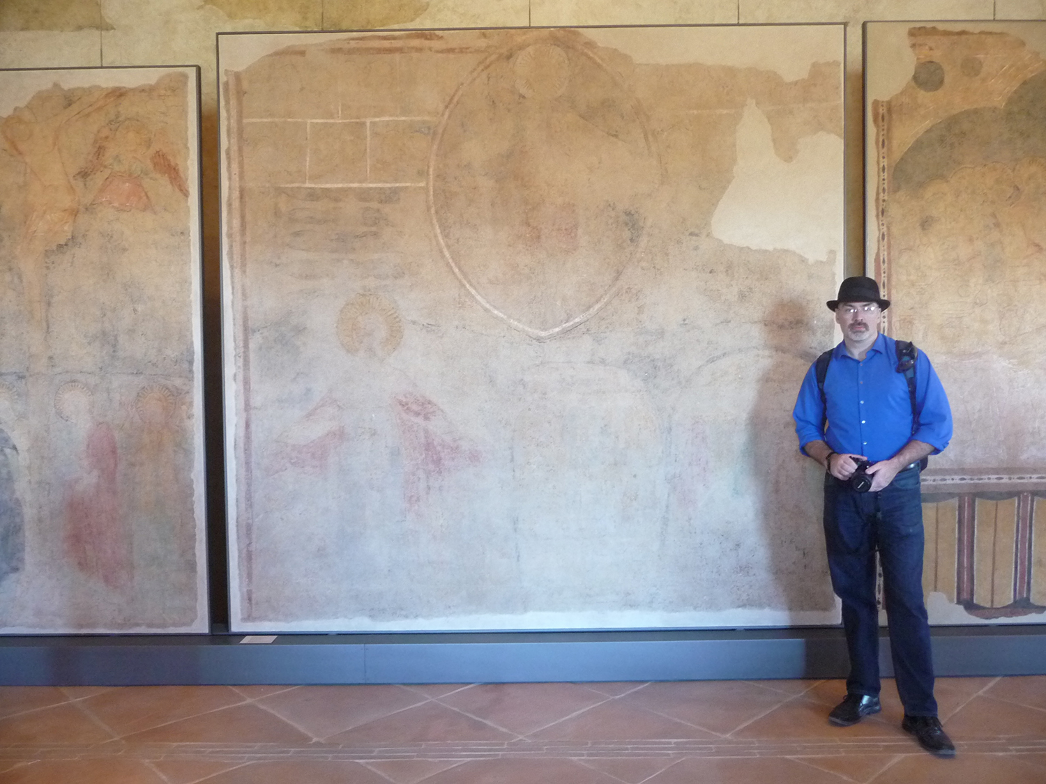 Figure 12. The author stands before a detached fresco—actually the layer of plaster and pigment remaining when the  Second Coming  fresco was removed from the wall of the monastery of Santa Maria inter Angelos, itself now detached and exhibited in the Museo Nazionale del Ducato, Spoleto. Photograph by Caroline Kline.