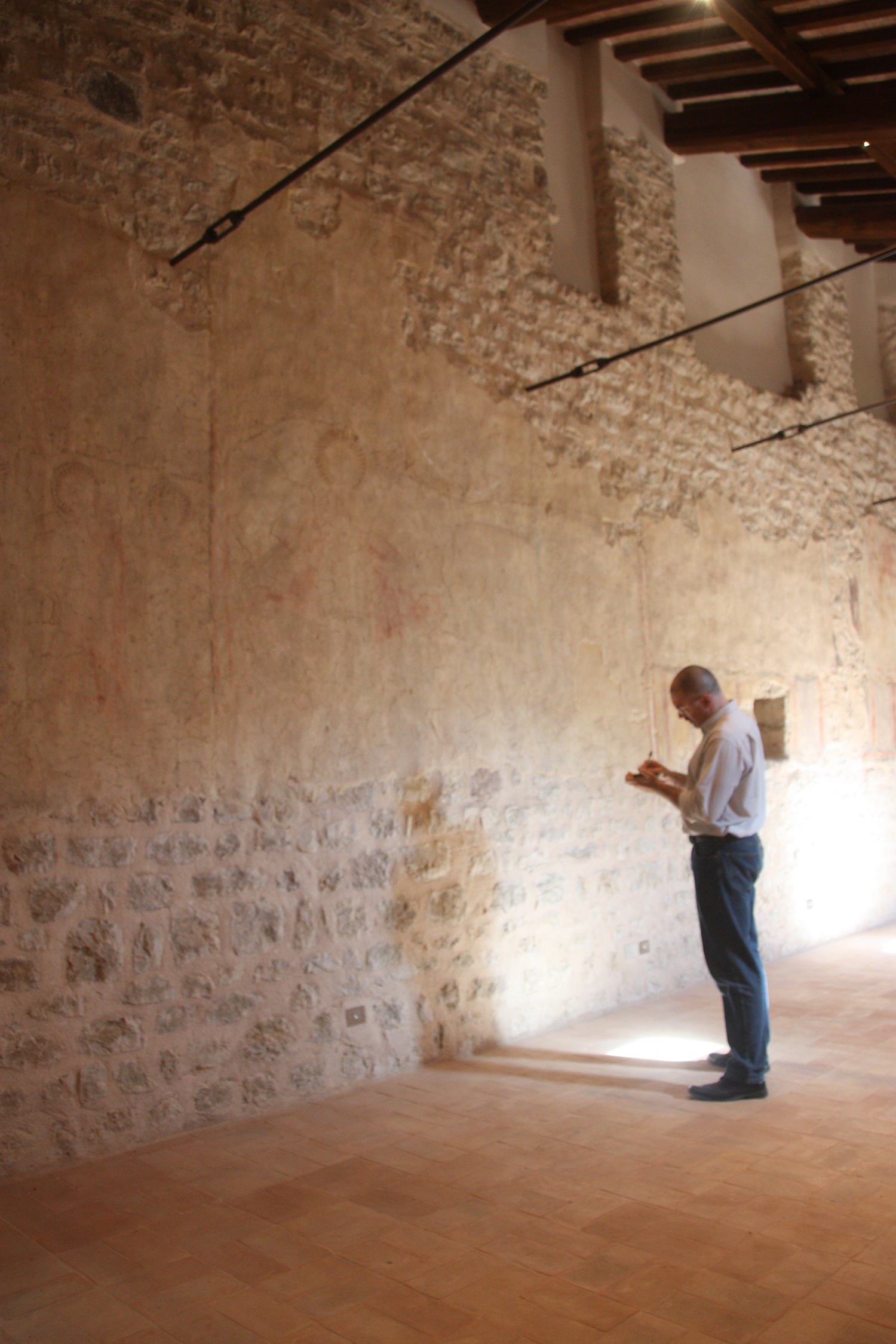 Figure 13. The author in the monastery of Santa Maria inter Angelos, facing the section of the north wall where the  Second Coming  fresco was originally located. Faint traces of pigment are visible in the preparatory plaster remaining on the wall, as are slight depressions that gave texture to the halo of Mary. Photograph by Caroline Kline.