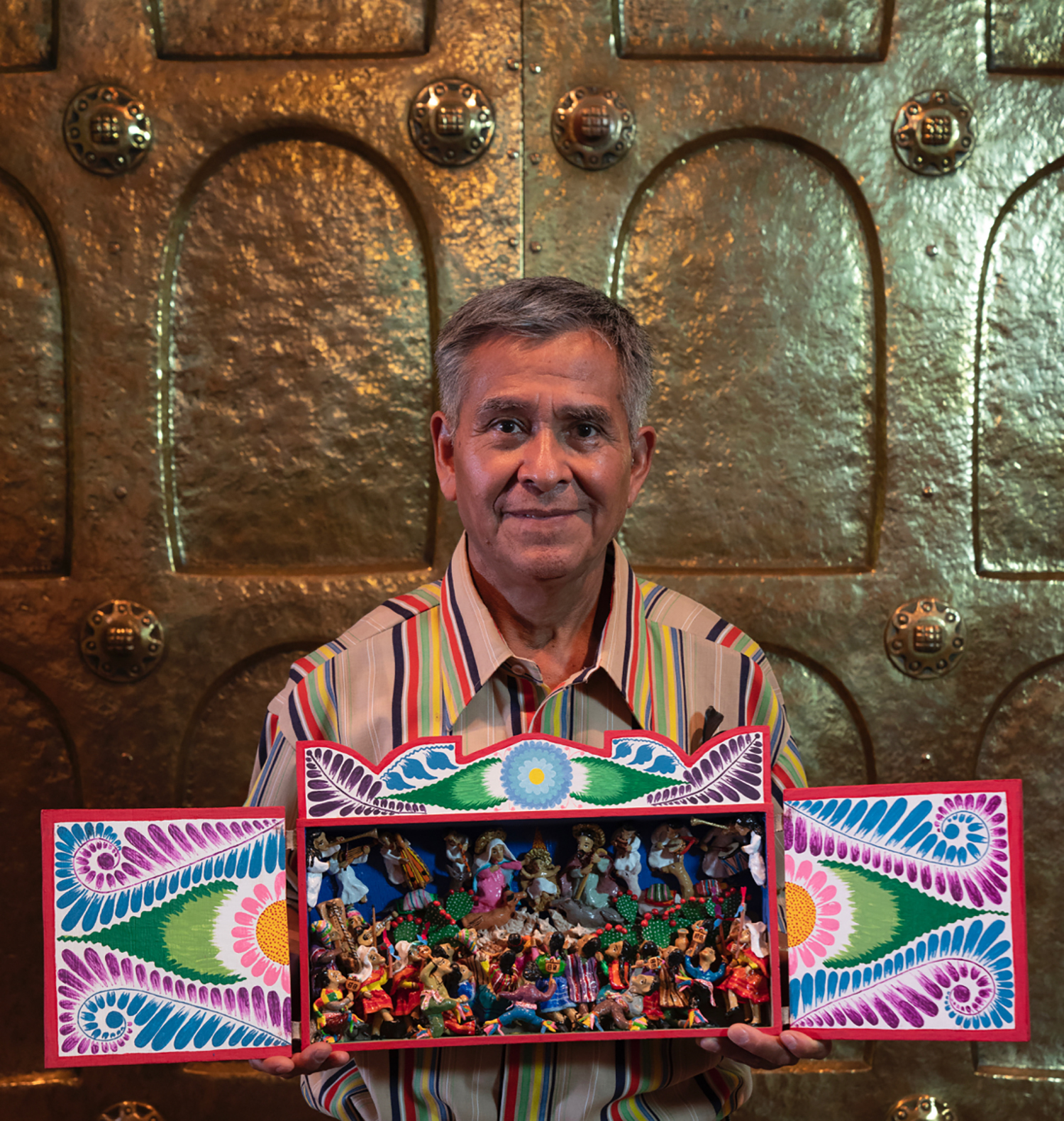 Figure 9: Jeronimo Lozano with a Nativity retablo in Glencairn's Great Hall, 2018. Lozano grew up and learned his craft in his native Peru; he now lives in Salt Lake City, Utah.