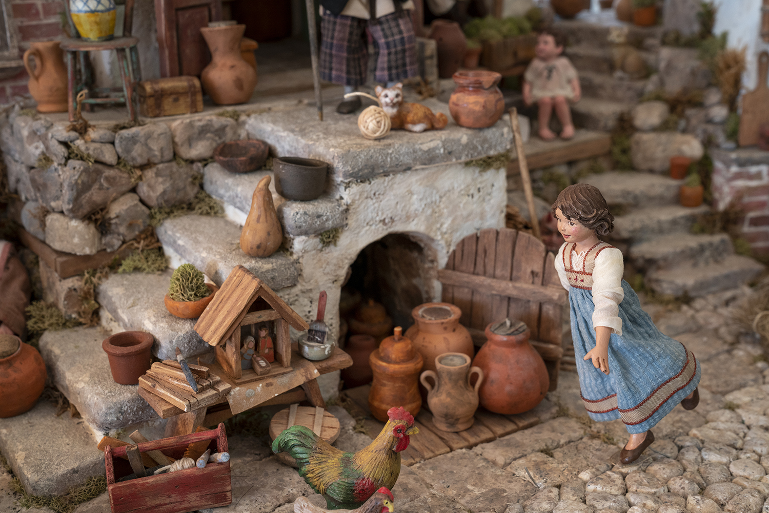 Figure 13: A young girl runs through her Italian village; a figure by Karen Loccisano. Note the small Nativity on the bench.