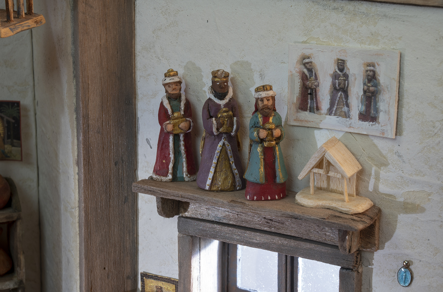 Figure 15: The wise men, an incomplete stable, and a blue pendant of the Virgin Mary. The pendant once belonged to R. Michael Palan's mother, and was added to her rosary beads.