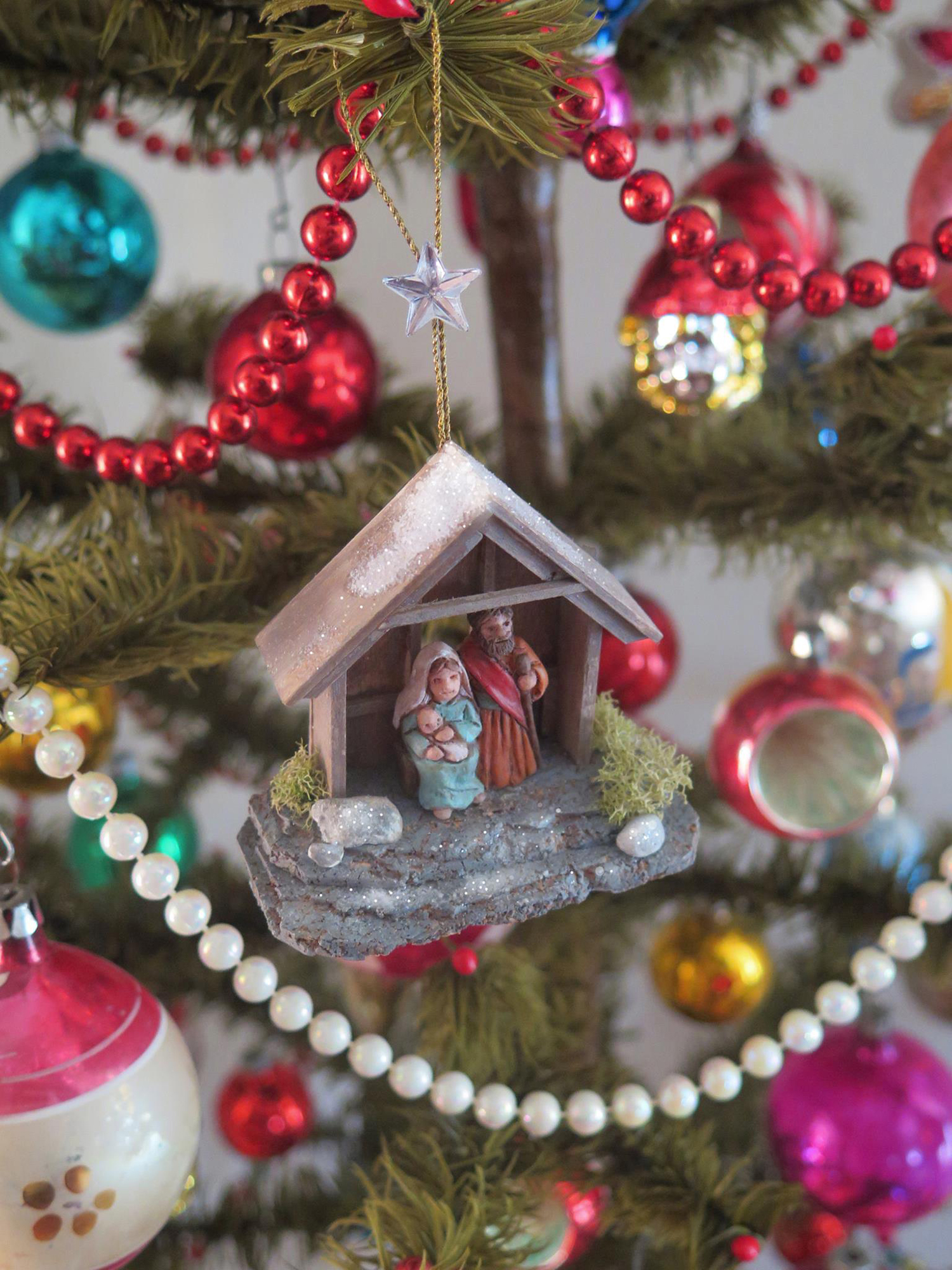 Figure 21: A example of a completed Nativity ornament, designed to be made by workshop participants, hanging on a Christmas tree. Photo by R. Michael Palan.