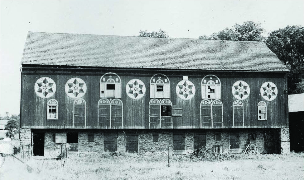 "Figure 13: Historic Lehigh County Barn, Photography by William Ferrell, ca. 1940, Pennsylvania German Cultural Heritage Center, Kutztown University.  Once called ""the most decorated"" in the region, this barn is located in New Smithville, Lehigh County, close to the border with Berks. The front forebay wall features three pairs of six-pointed repeating star patterns. Each door and window is crowned with a star and a pair of moons. On each gable end, there is a triad of star patterns with a small star in a white triangle appearing to shine down from just under the pinnacle of the roof, as if the other stars were projections of its light."