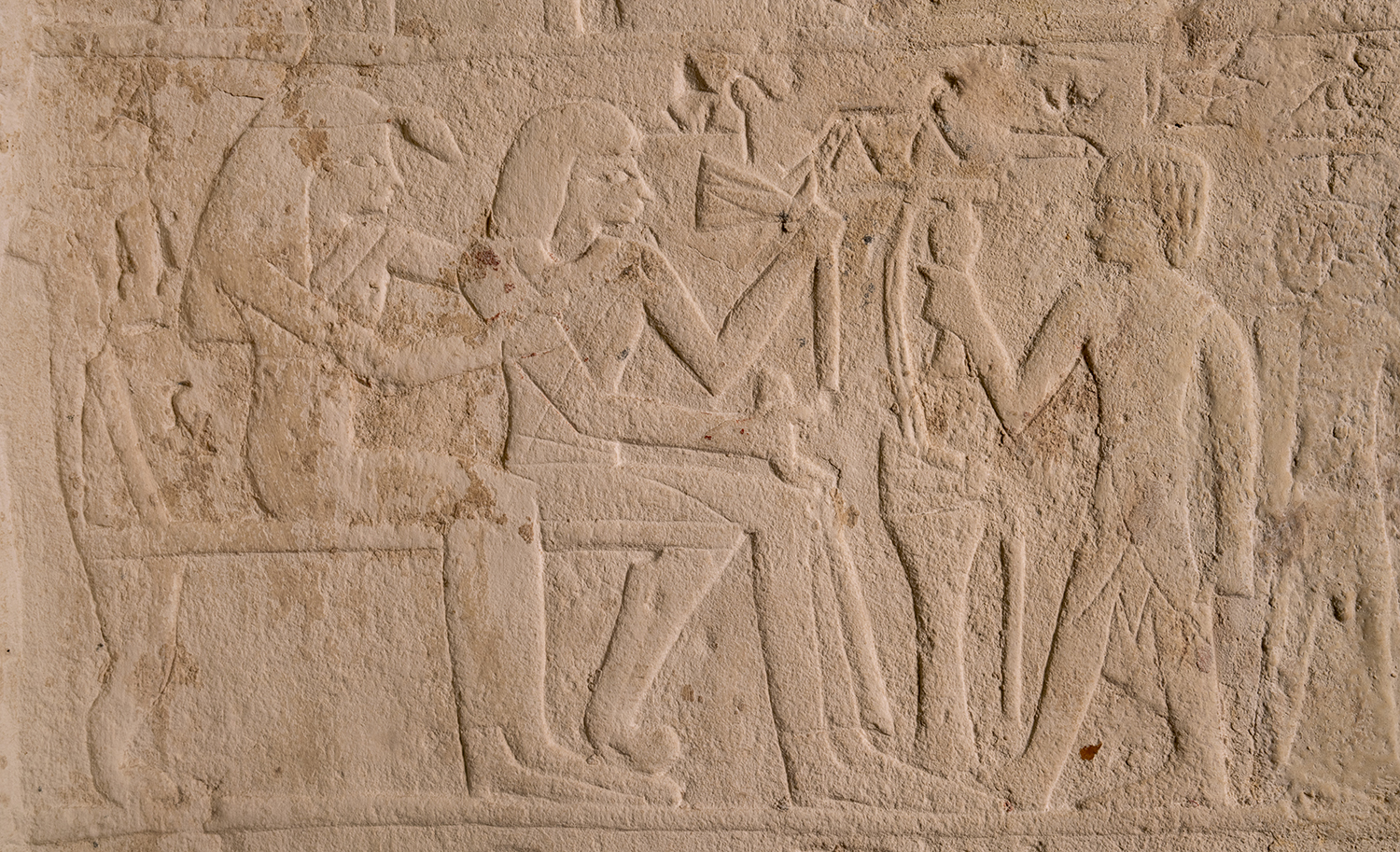 Figure 27: A detail from the stela of Maienhekau showing the deceased and his wife seated on chairs. In front of them, a son makes an offering to the couple.