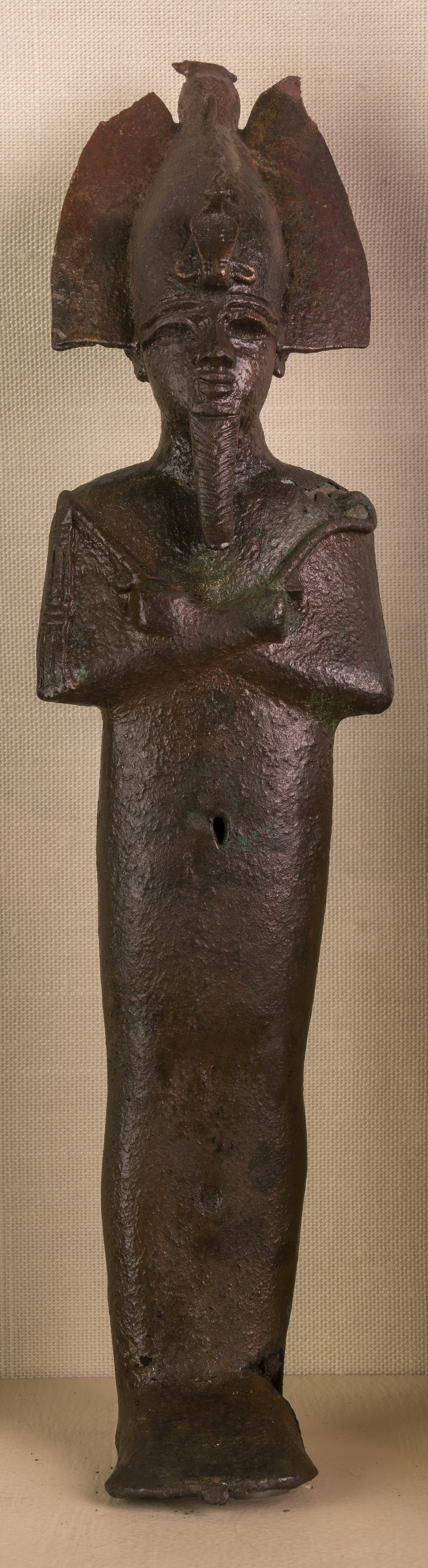 Figure 5: Bronze votive statuette of Osiris (E74). The god is shown mummiform, wearing his usual crown and holding the crook and flail as symbols of his kingship.