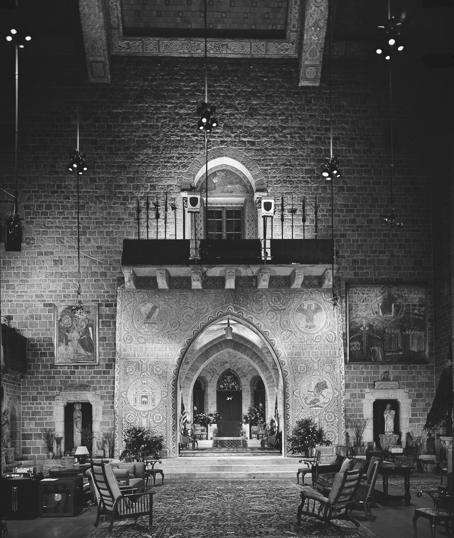 Figure 4: Photograph of Glencairn's Great Hall, taken when the Pitcairn family lived in the building. Works of authentic medieval sculpture, stained glass, and frescoes are integrated with 20th-century art created by craftsmen from Bryn Athyn Studios.