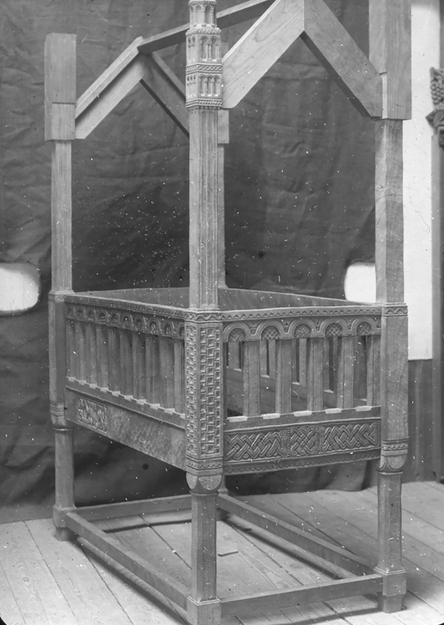 "Figure 14: Archival photograph of Lachlan Pitcairn's baby crib taken in one of the Bryn Athyn workshops. Some portions of the crib have been carved, while others are still unfinished. A closer look at some of the uncarved portions reveals the use of an adze to give the wood ""irregularities similar to hand-hammered metal"" (Cooke 1987, 315; see full quotation below)."