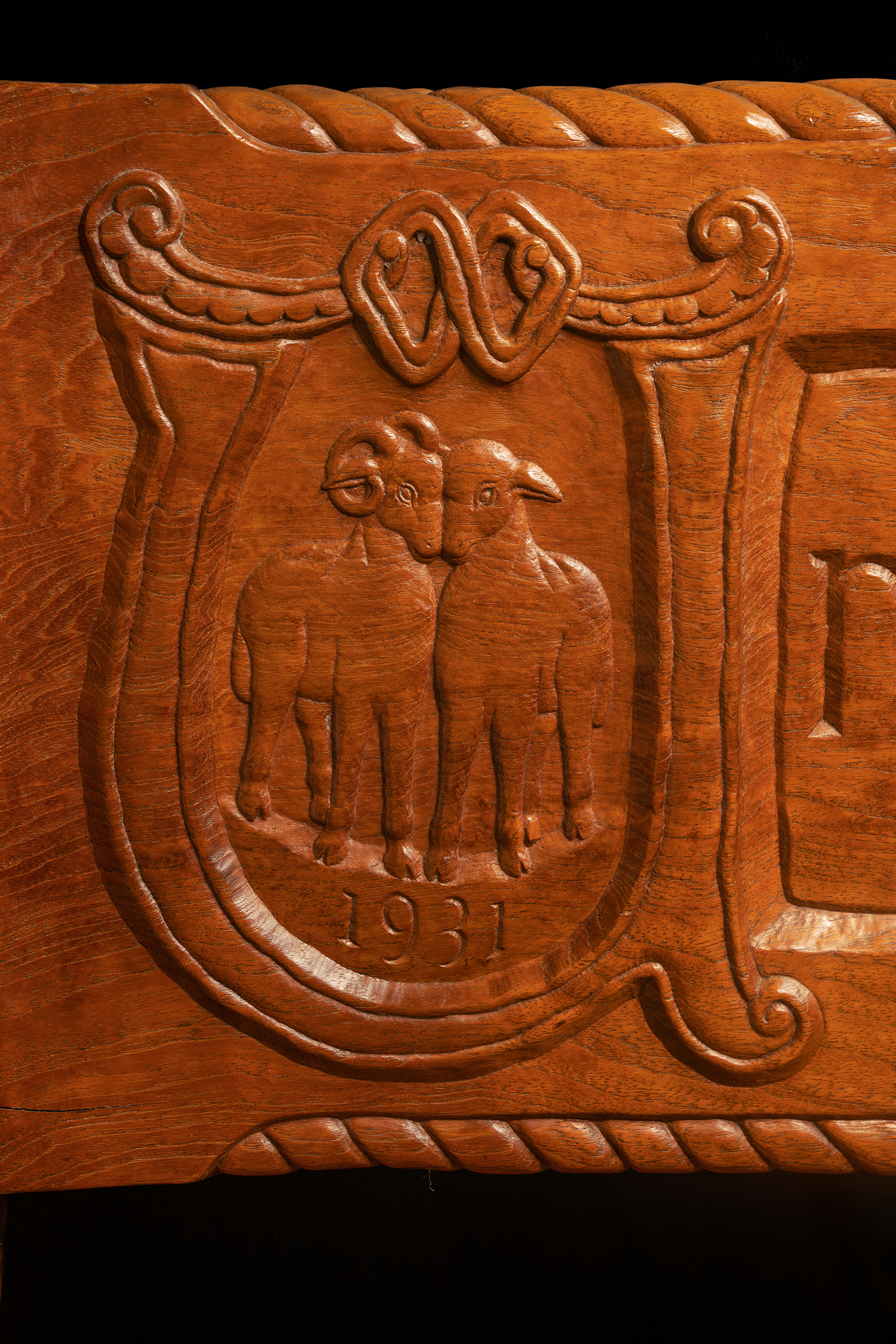 "Figure 17: A quotation taken from the wedding ceremony of Raymond and Mildred Pitcairn is carved around three sides of the base of their bed. Here a ram and ewe, a symbol for husband and wife, are enclosed by the initial letter ""U"" beginning the quotation. The date of the bed's completion—1931—is incised below the ram and ewe."
