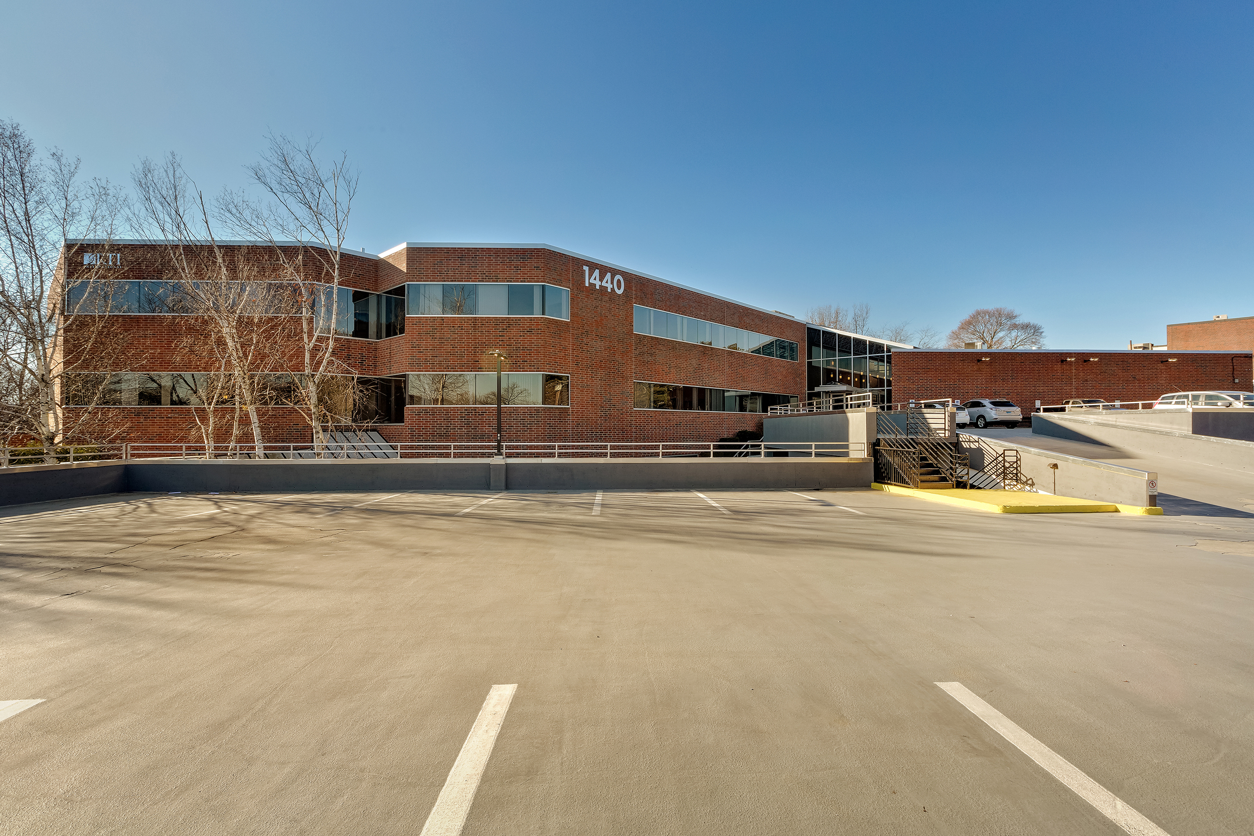 New image with updated windows, frames, roof and edge metal, parking garage façade and signage