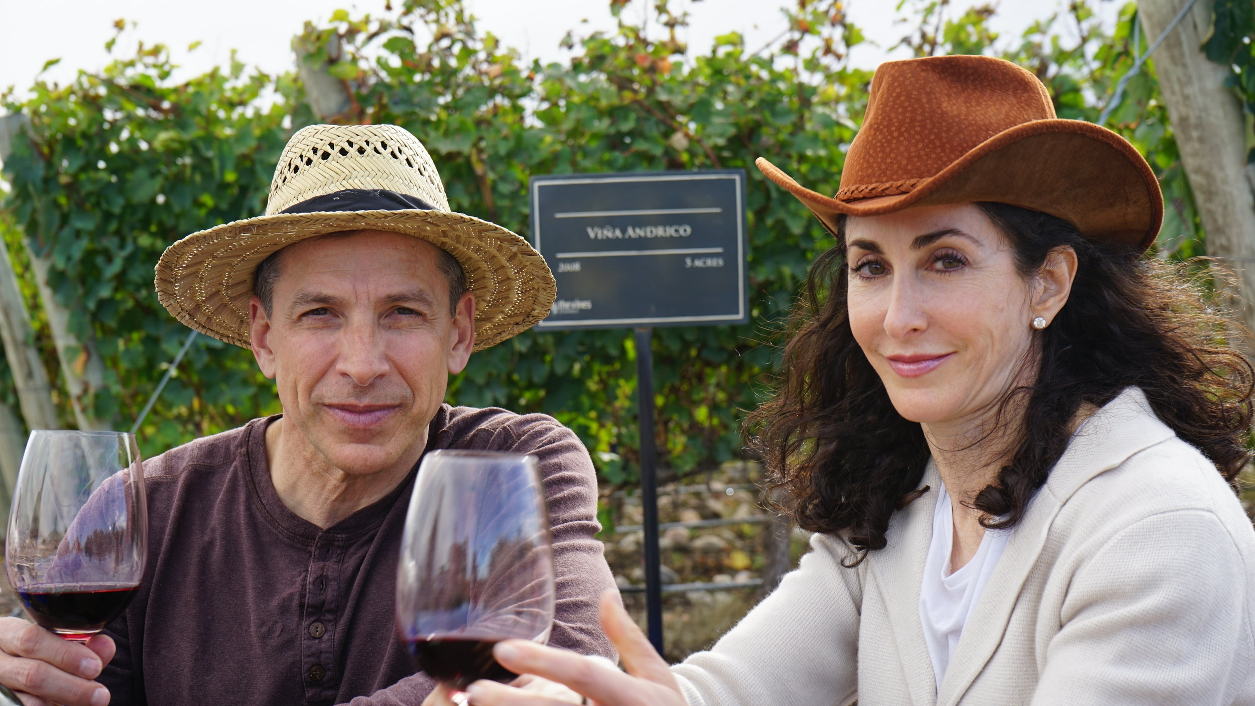 Proprietors Richard and Andrea Saperstein tasting the wine in the vineyard.  Vina Andrico vineyard in Mendoza, Argentina.