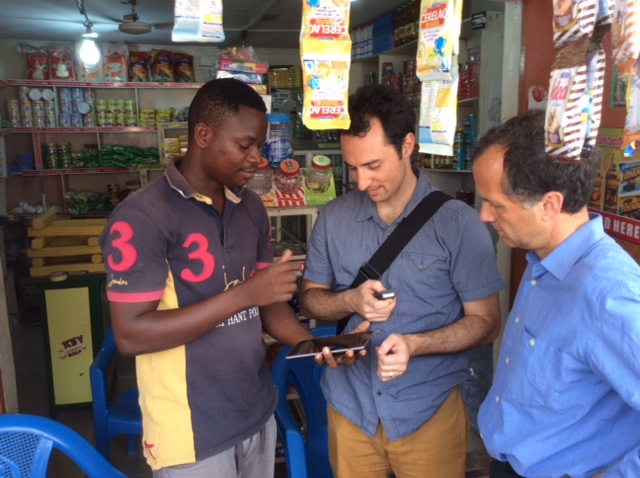Shopkeeper in Accra showing BFA team how he uses smartphone app to run his business