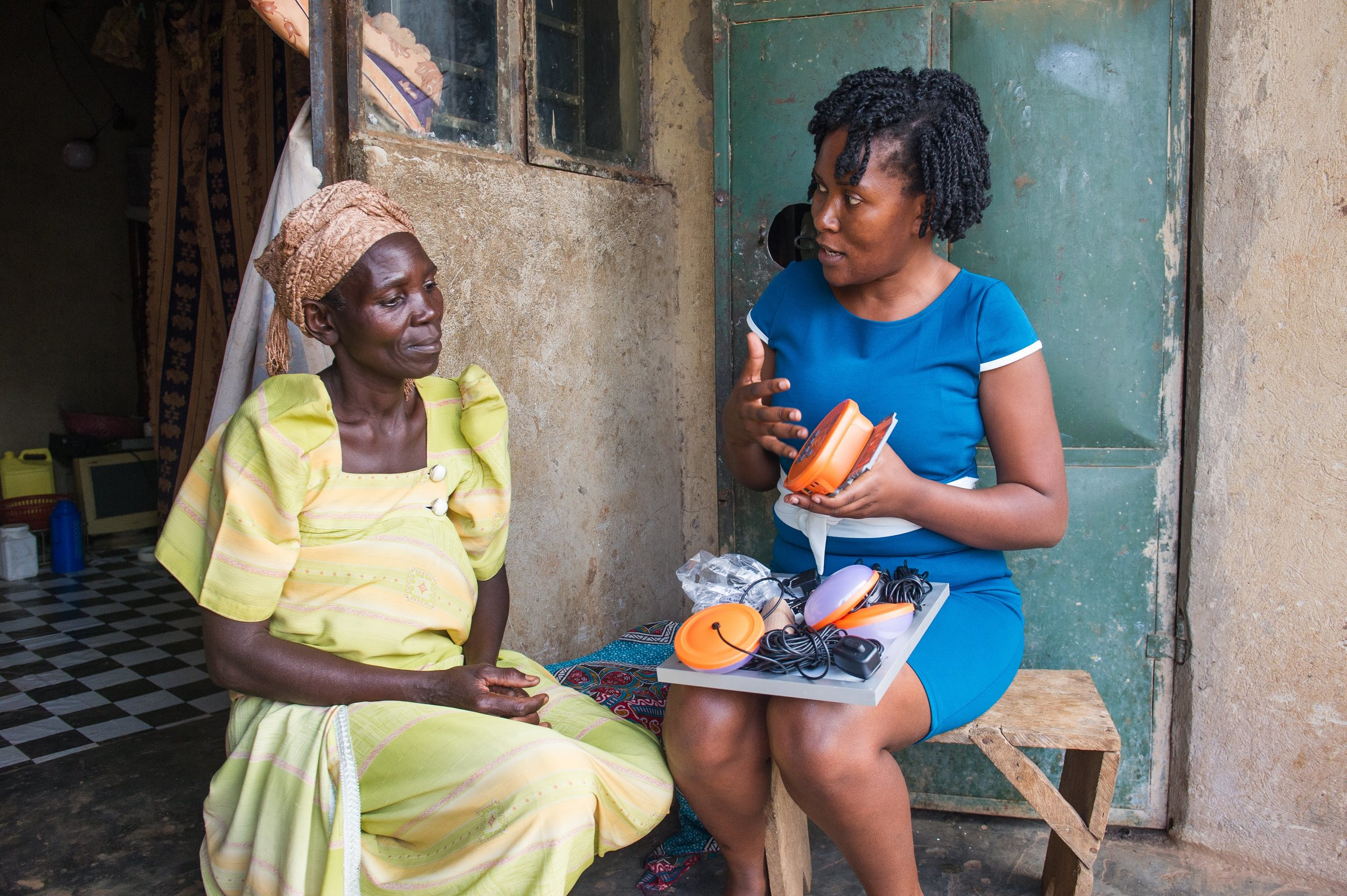 Jane Namusisi, a 54-year-old Ugandan woman, meets with BrightLife field supervisor, Brenda Nansasi, to discuss installation of a new solar home system. Photo credit: Dawn Deeks