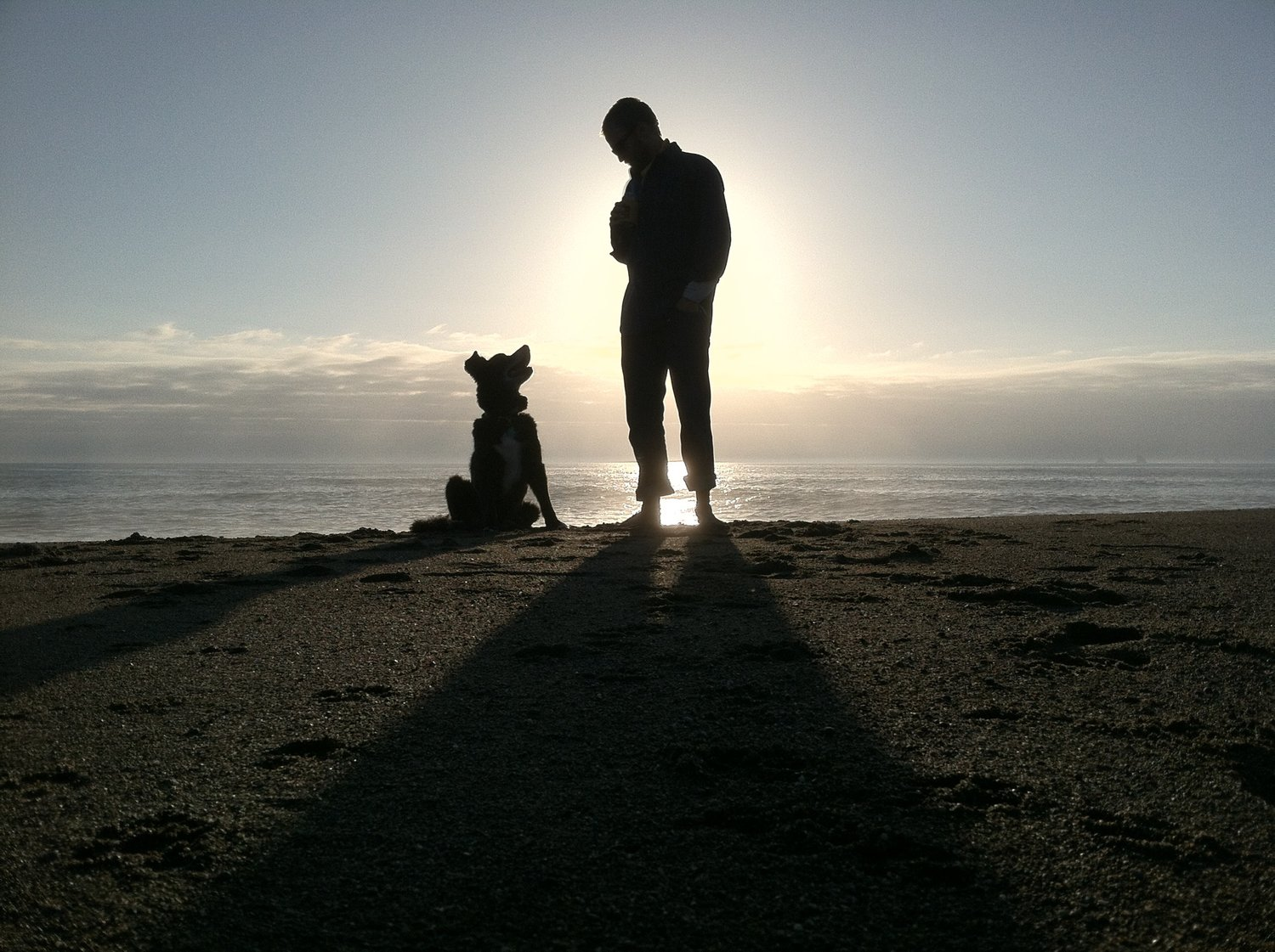 dan kirk and his dog on beach at sunset