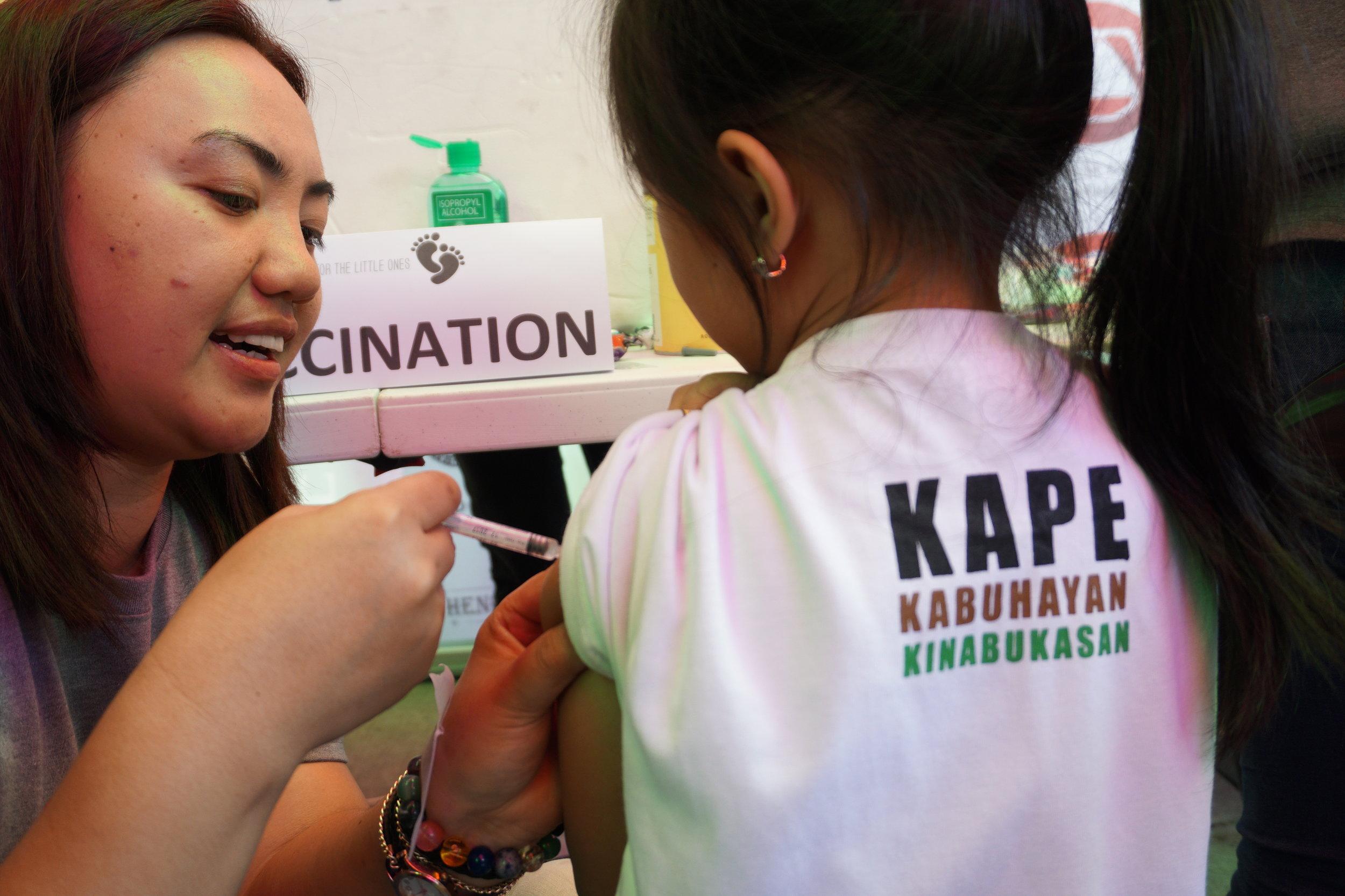On photo:    Child Development Volunteer Sherr-an C. Karry, RN-NSB administering flu vaccine