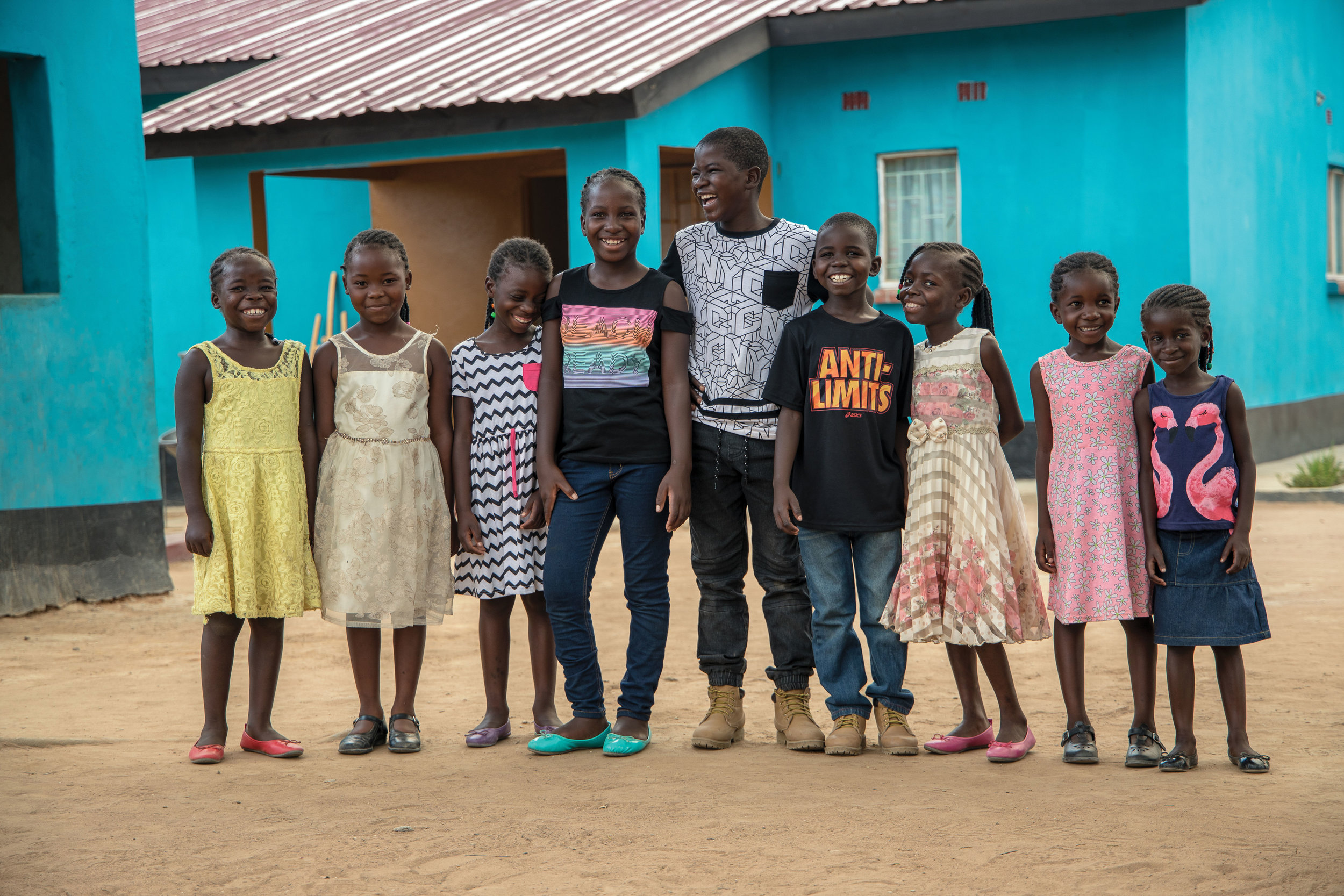 The children in front of their Life Okendewa home (the Love Abounds home for orphaned and abandoned children). L to R: Esther, Hope, Sharon, Frieda, Godfrey, Evans, Josephine, Juliette, and JoJo.