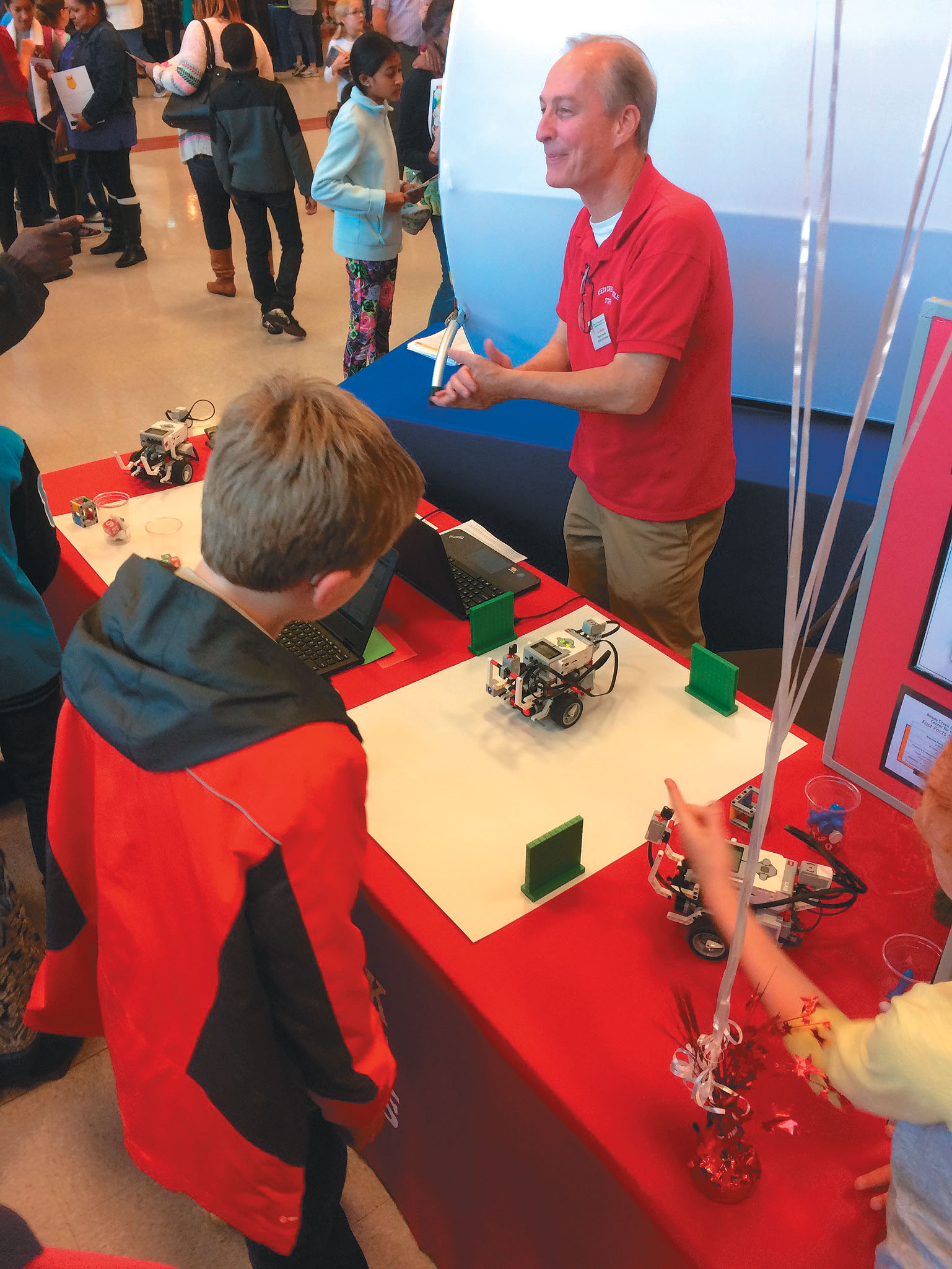 reedy creek magnet middle school mechatronics teacher ron boehm speaks to students at the magnet, early college, and year round schools fair at southeast raleigh magnet high school. Photo by thomas cooper/christine sachs