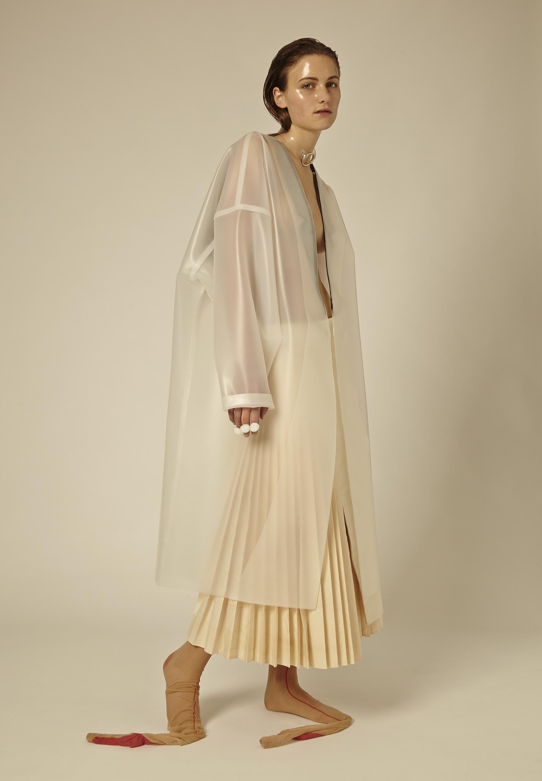 Latex coat by Xun Li, BFA Menswear Design. Skirt by Ruone Yan, BFA Menswear Design. Necklace, model's own. Stockings, stylist's own.