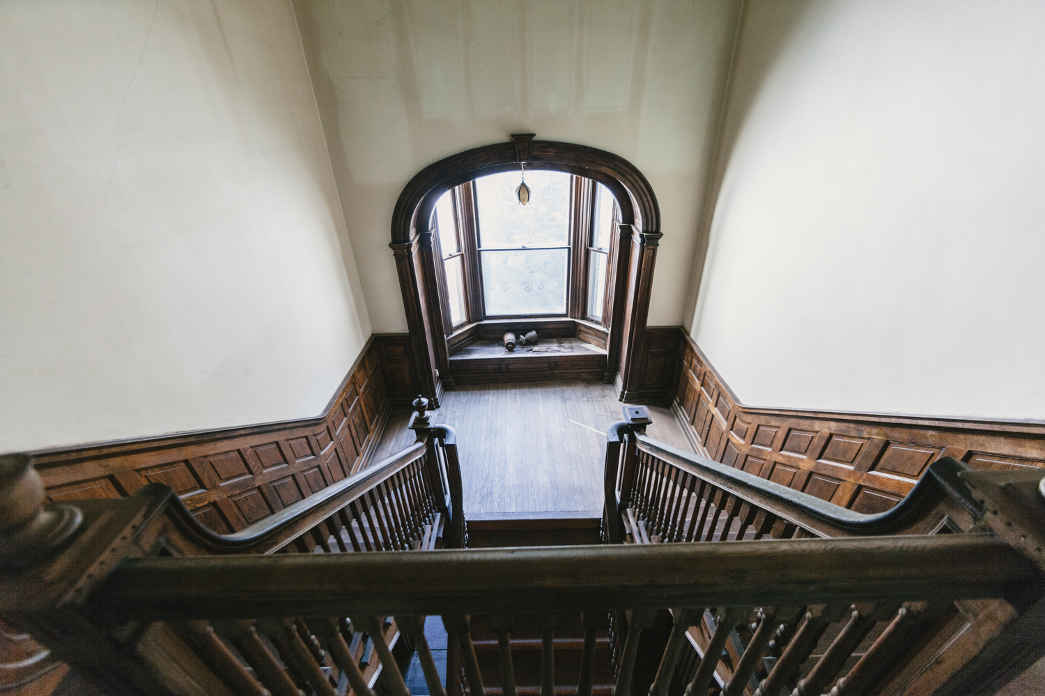 The split staircase down to the window seat overlooking the back garden then uniting to enter the foyer