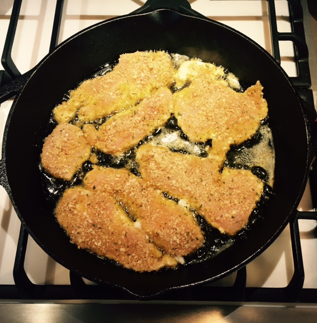 Chicken cutlets cooking in olive oil