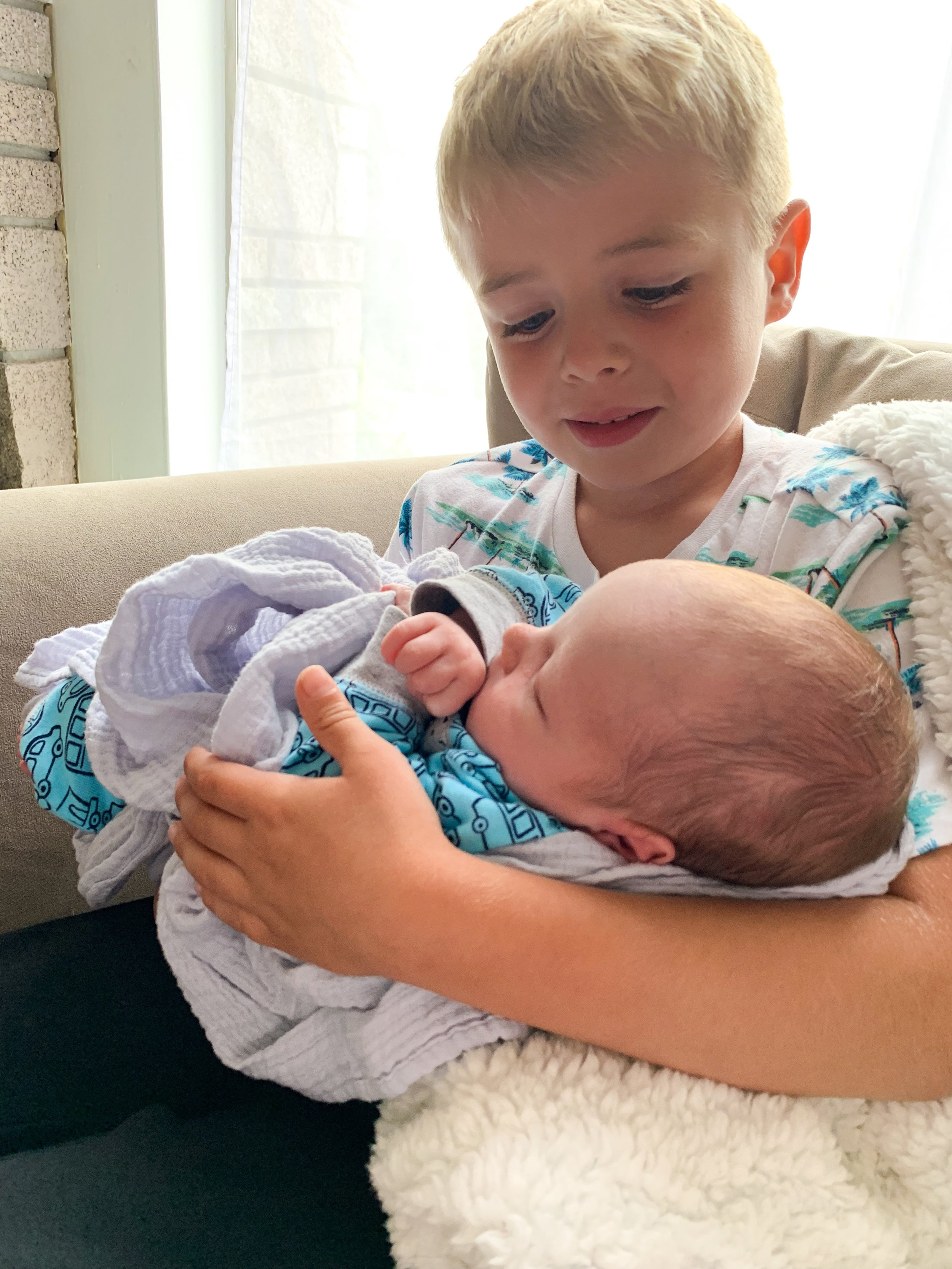 Older brother (my sweet stepson, Carter) holding his little bro for the first time.