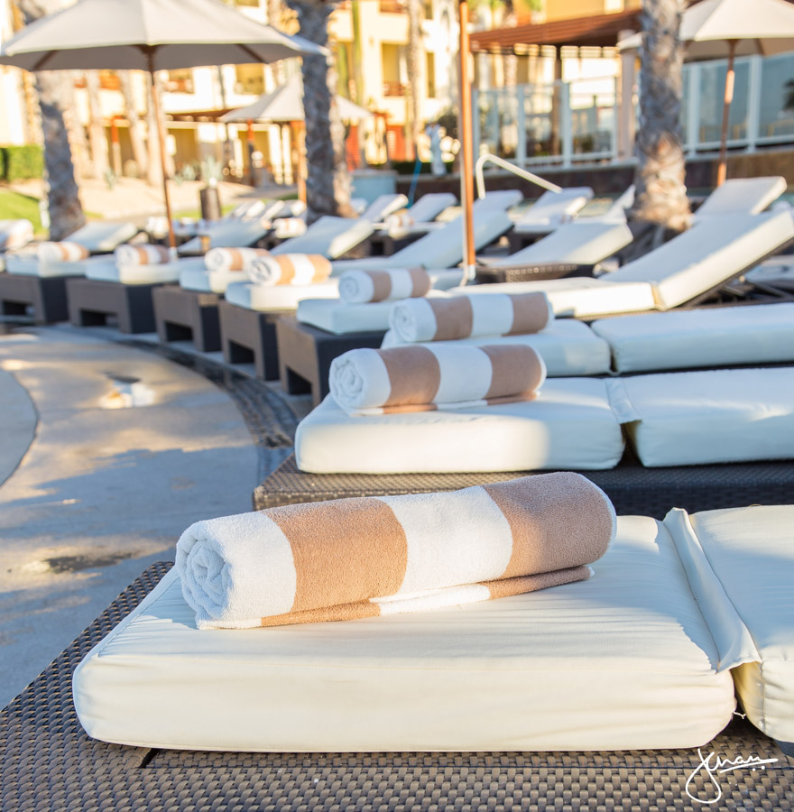 Perfectly rolled up towels on pool loungers
