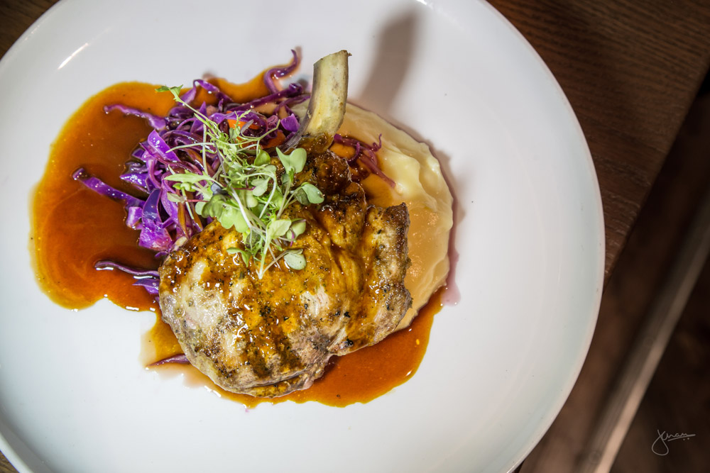 Carlton Farms Pork Chop - red cabbage, black garlic, carrot, beecher's cheddar yukon potato, peppercorn sauce