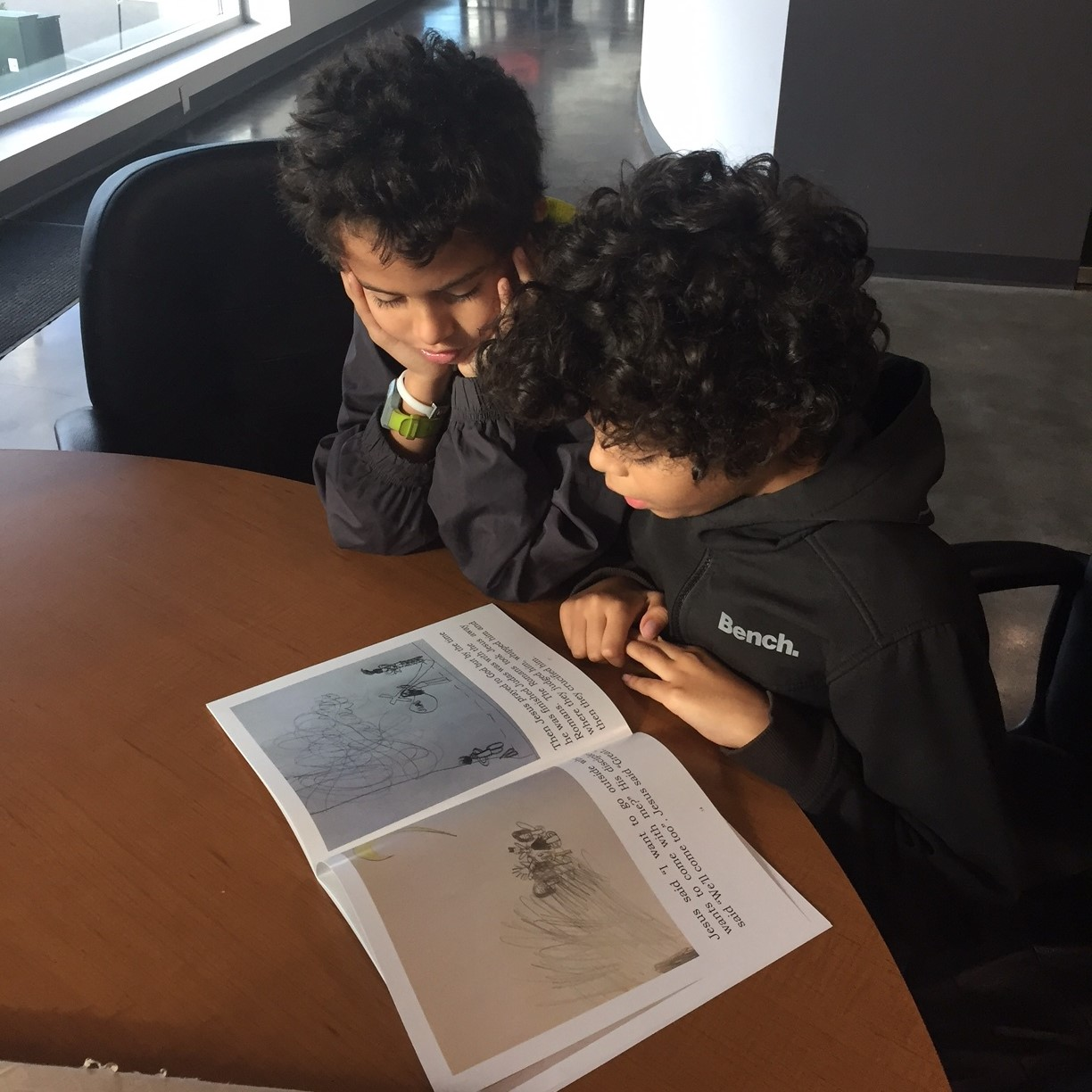 "This is Amos and Jaguan doing a final read of their first book called ""Jesus"" before having copies made."
