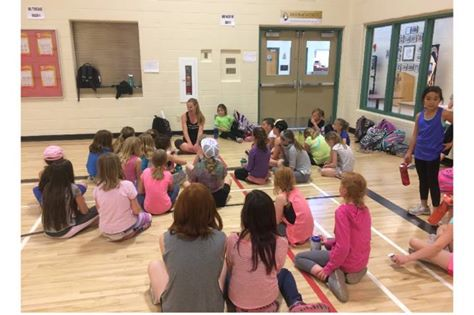 Kelsey speaking to a girl running group at a local school