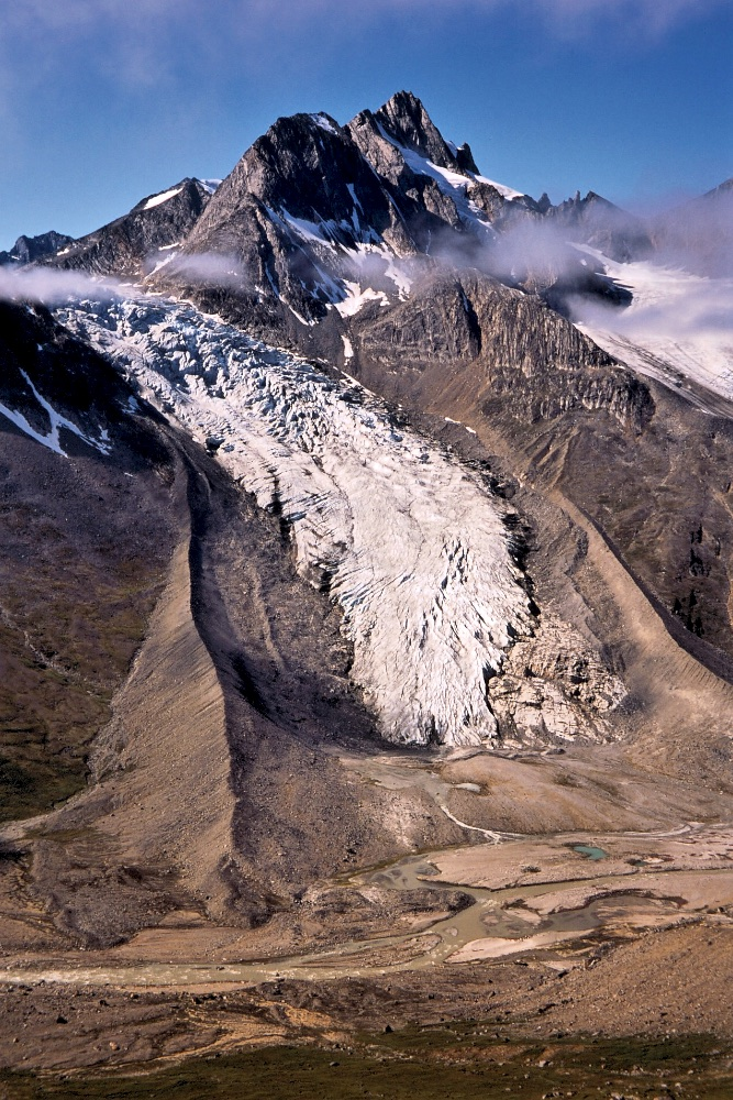 A glacier spills down into the Tasiilap Kuua Valley
