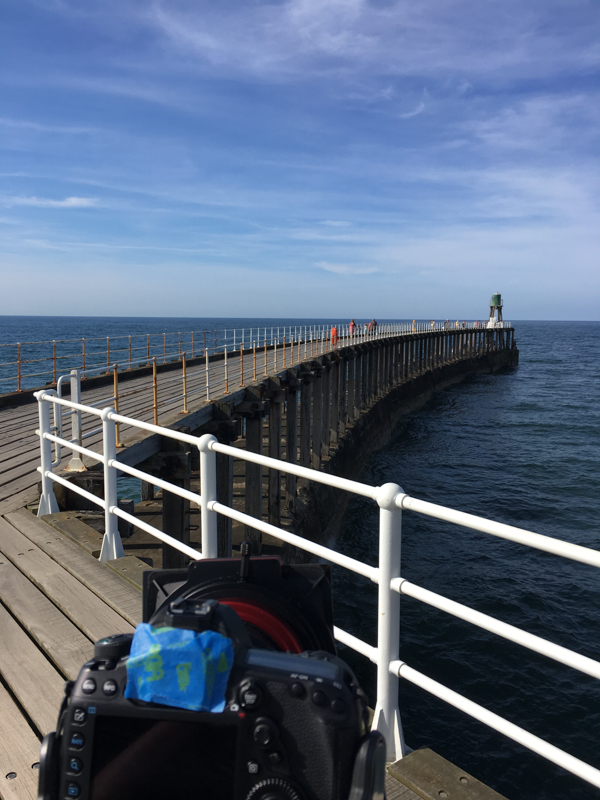 Behind the scenes - there are people walking along the pier at Whitby