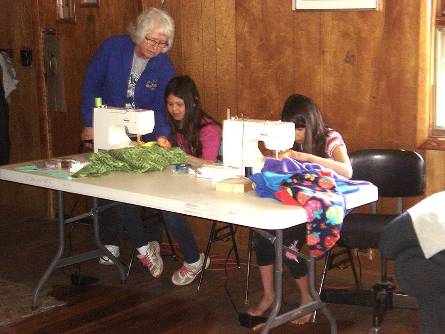 WEB Volunteer teaching 2 girls to sew