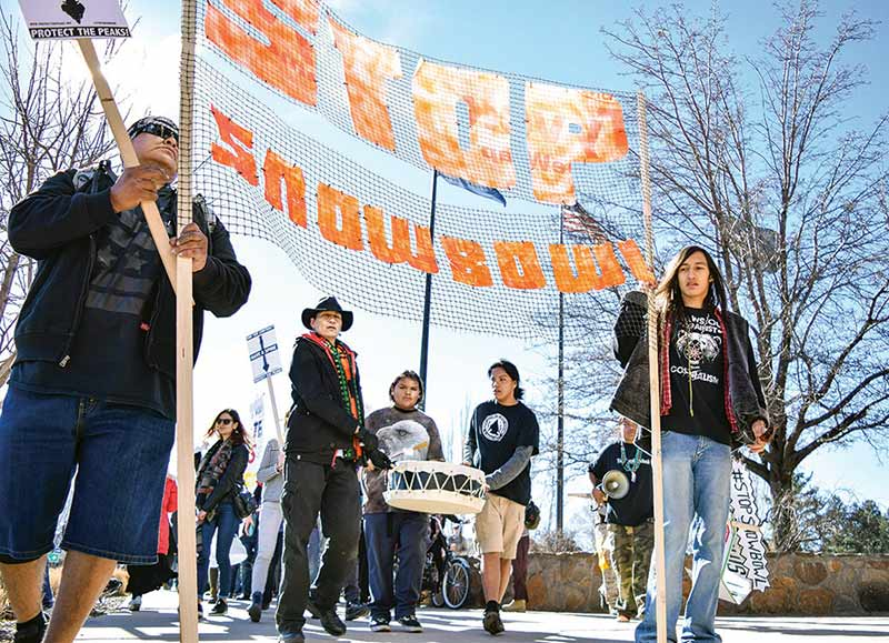 More than 50 demonstrators march across downtown Flagstaff on Jan. 14 urging the city council to end the city's contract with the Arizona Snowbowl ski resort, which uses 100 percent effluent to make artificial snow. Photo credit: Krista Allen, Navajo Times