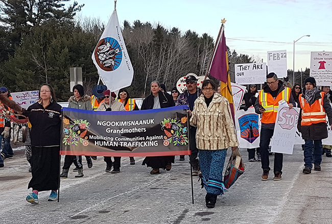 Ngookimisnaanuk Grandmothers Council members Alison Recollet (L) and Marly Day-Bateman lead peaceful march along Hwy 17B – Garden River Ontario – Human Trafficking Awareness Day Feb.22nd, 2018.