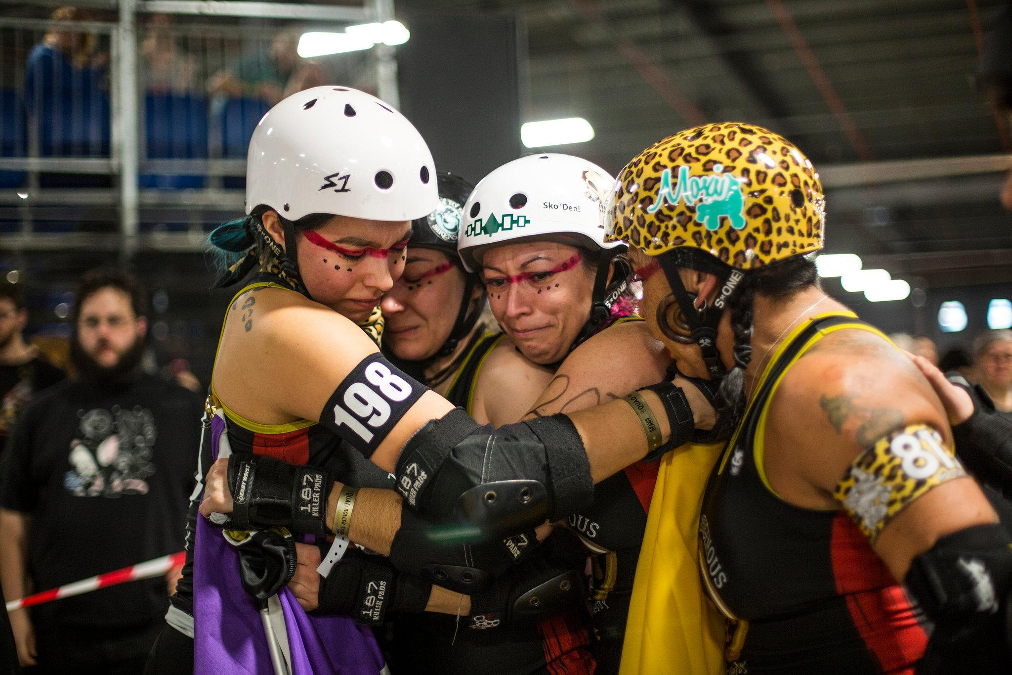 """From left, Ms. Ghosen; Amil Dupuis-Rossi, a.k.a. """"The Fighting Mongoose""""; Michelle Cross, a.k.a. """"Squarrior""""; and Ms. Bontkes of Team Indigenous hugged before their last World Cup roller derby game. Photo Credit: Rachel Clara Reed for The New York Times"""