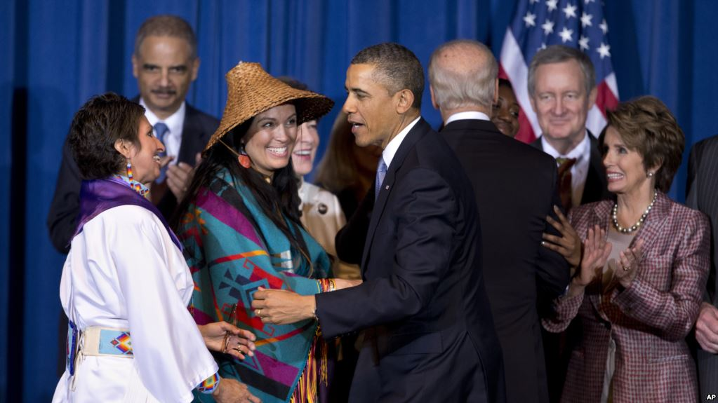 President Barack Obama greets Our Sisterís Keeper Executive Director Diane Millich, from left, and Tulalip Tribes of Washington State Vice Chairwoman Deborah Parker, after signing the Violence Against Women Act in Washington, D.C., March 7, 2013. Five years after a federal law gave tribes authority over non-Natives for some domestic violence crimes, public safety advocates say communities are empowered to report wrongdoing and governments are working better together. Photo credit: VOA File
