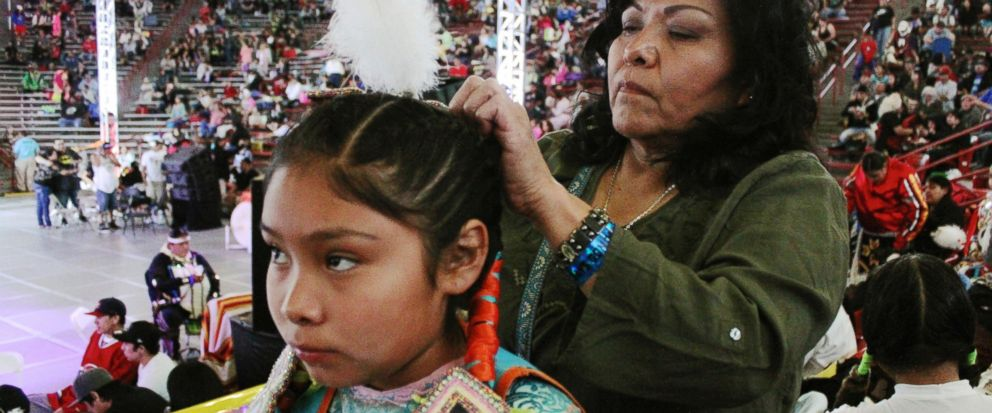 In this April 24, 2015, file photo, Yvonne Grinnell, right, attaches a feather to Tasia Pecos' hair in preparation for the grand entrance at the 32nd annual Gathering of Nations in Albuquerque N.M. The Gathering of Nations, one of the world's largest gatherings of indigenous people, is set to begin Friday, April 27, 2018, in Albuquerque. The annual event attracts around 3,000 dancers from hundreds of tribes in the U.S., Canada and Mexico and generally draws about 80,000 visitors with dances, drum contests and various competitions. (AP Photo/Susan Montoya Bryan, File)