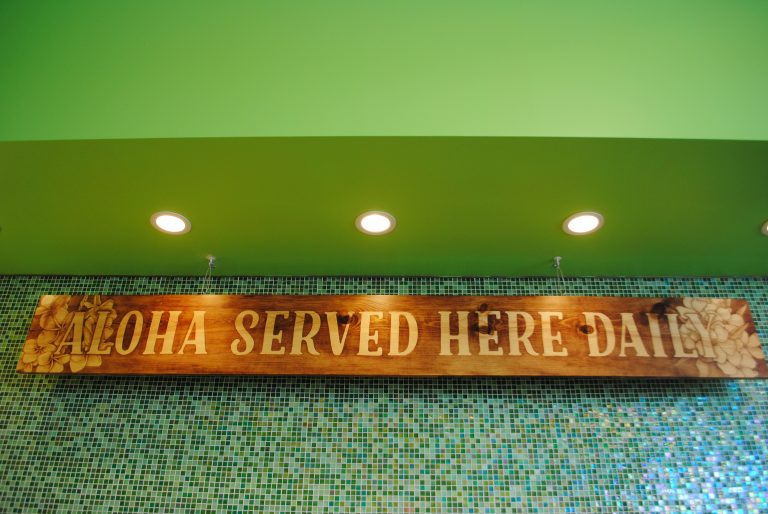 Tasha Kahele had to replace signs, menus, and advertisements after being forced to re-brand her poke shop. (Emily Russell/Alaska Public Media)