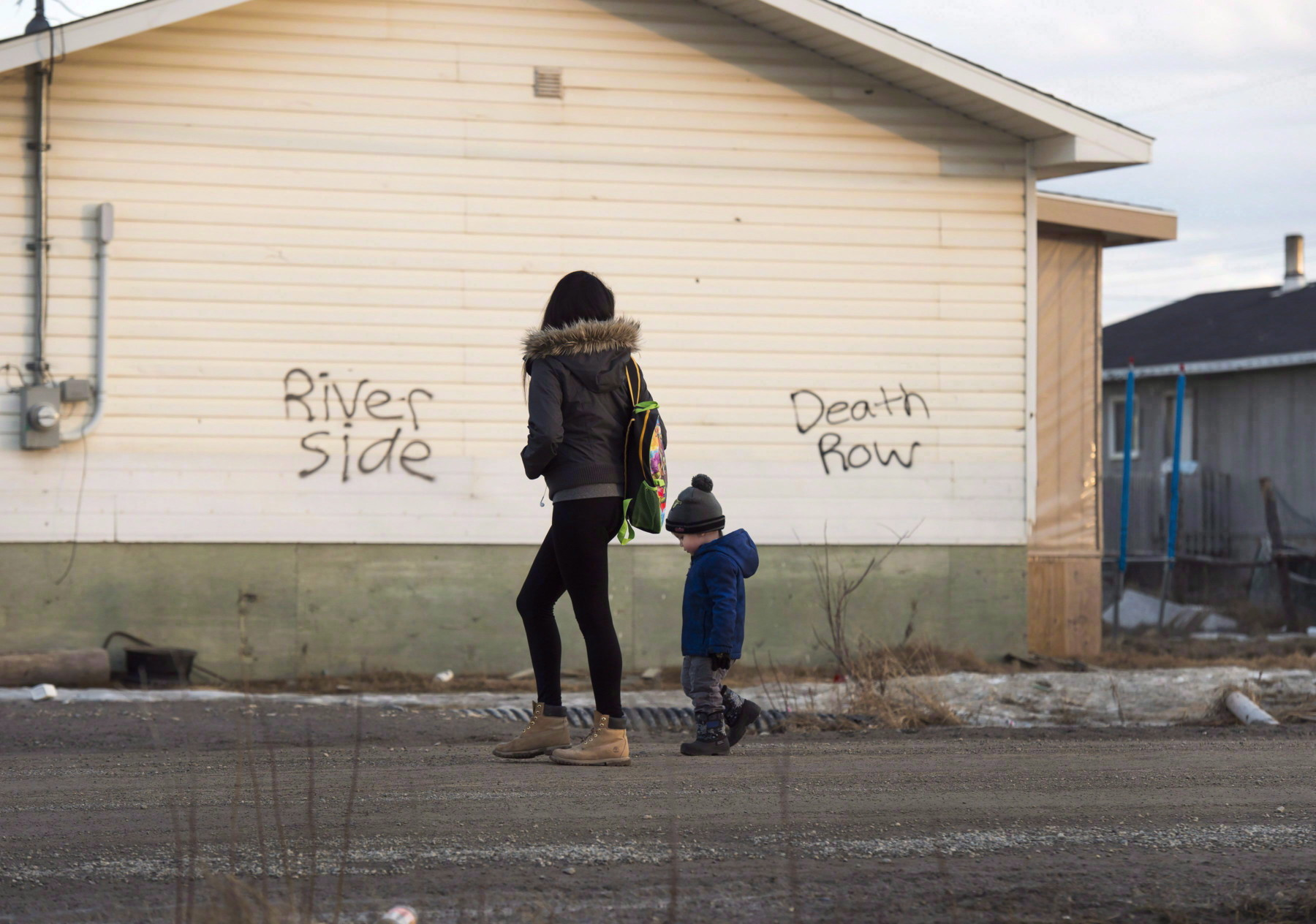 A woman and a child walk through the streets in the community of Attawapiskat, Ont., on April 16, 2016. THE CANADIAN PRESS/Nathan Denette lutheran indian ministries native news