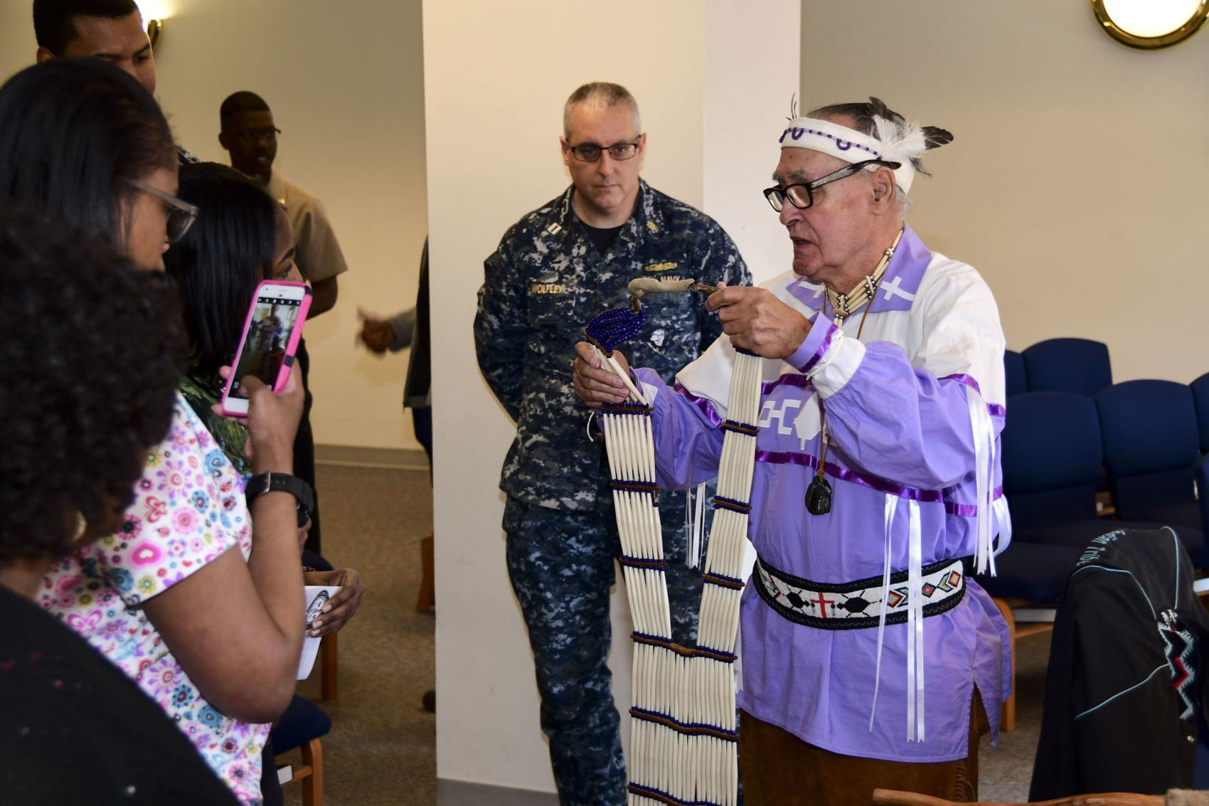Pastor William M. Reid, a member of the Meherrin Indian tribe of North Carolina, presents handmade Native American wardrobe items during Naval Medical Center Portsmouth's (NMCP) Native American Heritage Month celebration. Petty Officer 2nd Class Kris Lindstrom
