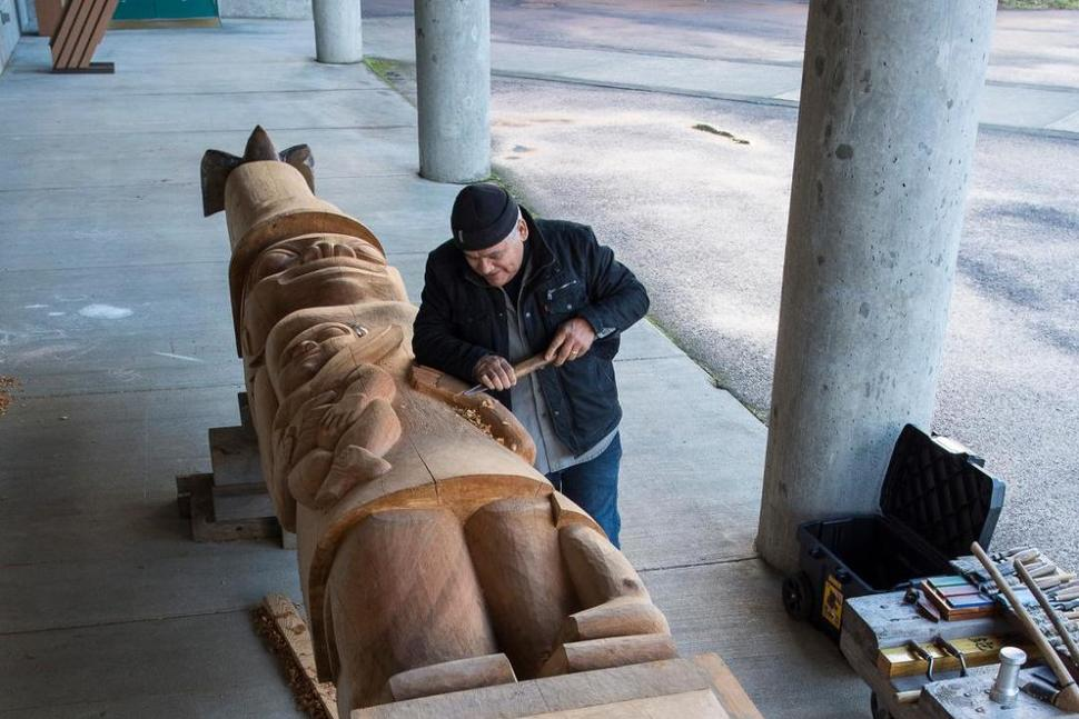 In this photo taken Oct. 31, 2018, Wayne Price, master Tlingit carver and associate professor of Northwest Coast arts and sciences, works on a healing pole at the University of Alaska Southeast in Juneau. (Michael Penn/Juneau Empire via AP)