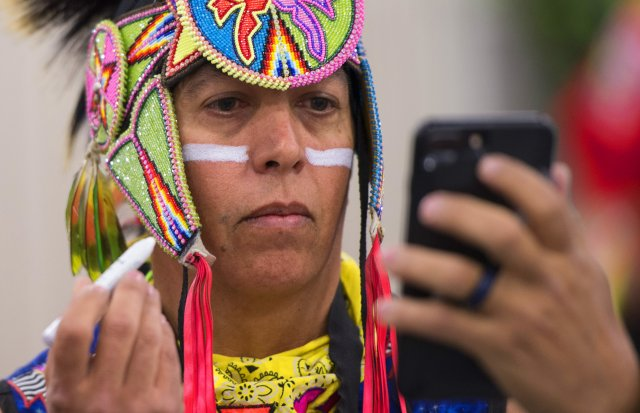 Army veteran Brian Hammill of the Ho-Chunk Nation applies face paint before grand entry at the 28th Annual Heard Museum World Championship Hoop Dance Contest at the Heard Museum in Phoenix, Arizona, Feb. 10, 2018. In the public Native American hoop dance performance, dancers can use up to 50 hoops to make formations that when combined convey a story. (Photo Credit: Mass Communication Specialist 2nd Class Anita C. Newman) lutheran indian ministries native news