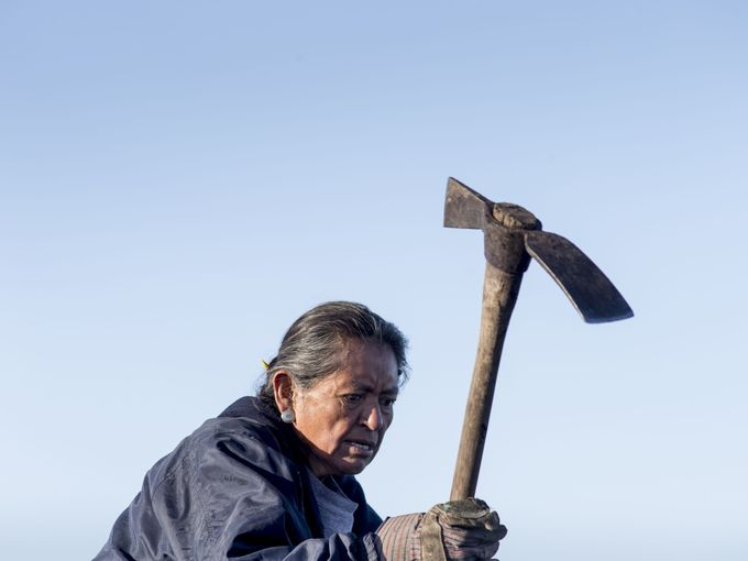 Charlotte Begay, 64, of Shonto, Ariz., breaks up coal with a pickaxe at the public loadout facility at the Kayenta Mine on Feb. 4, 2017. The mine's sole customer is the Navajo Generating Station, a coal-fired power plant near Page, Ariz. If the power plant shuts down it not only would impact plant workers, but coal miners as well. Mark Henle/The Republic