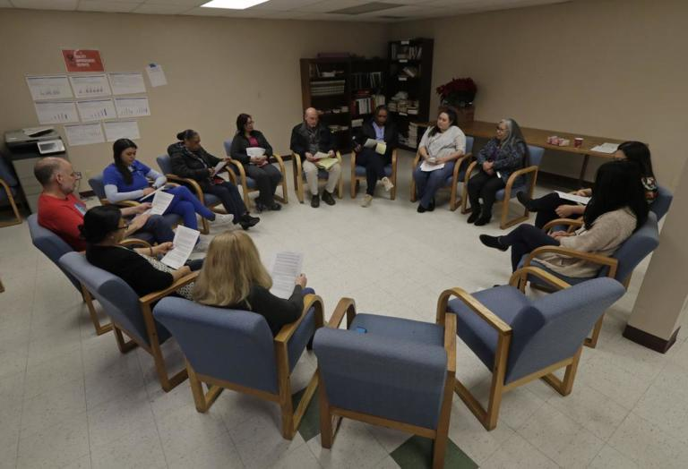 Annette Squetimkin-Anquoe, third from right, a member of the Colville Indian tribe and the Chief Traditional Health Officer at the Urban Indian Health Institute in Seattle, leads a talking circle meeting Friday, Jan. 11, 2019, to discuss the practice of traditional Indian medicine, including blessings and smudging, with employees of the Seattle Indian Health Board. Fallout from the federal government shutdown is hurting hundreds of Native American tribes and entities that serve them. The pain is especially deep in tribal communities with high rates of poverty and unemployment, and where one person often supports an extended family. (AP Photo/Ted S. Warren)